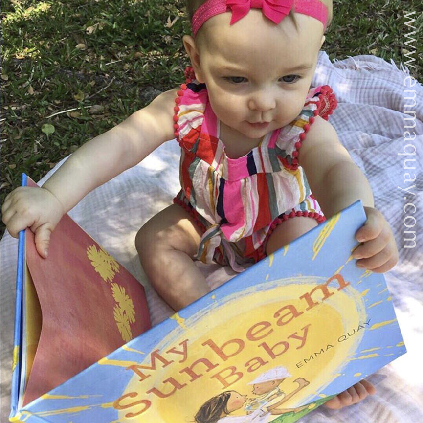 Olivia reading MY SUNBEAM BABY in the shade, a picture book by Emma Quay (ABC Books) - www.emmaquay.com