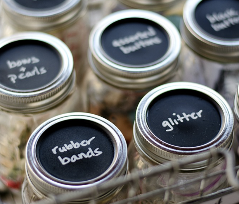Here is a great one for all the little bits & bobs that float about: paint the top of a mason jar with chalkboard paint and write the name in chalk or white craft pen. - Image courtesy of www.itallstartedwithpaint.com