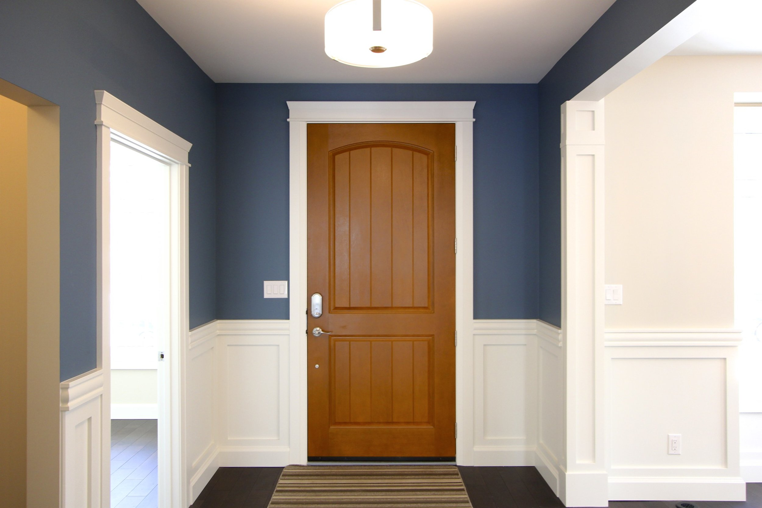 Metric Design Centre, Interior Design, Saskatoon, Residential Design, New Home Build, Custom Millwork, Transitional Design, Blue Feature Wall, Wood Front, Door, Front Entry, White Molding and Trim, Hardwood Flooring, Lighting.jpg