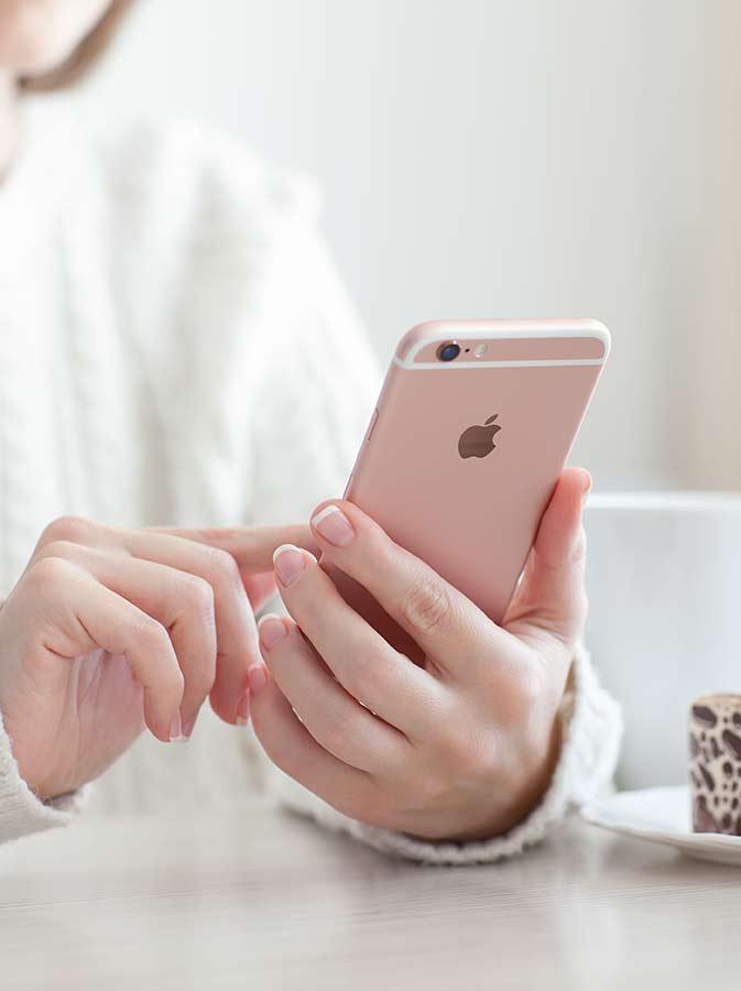bigstock-Woman-Holding-Iphone--S-Rose--106047935web.jpg