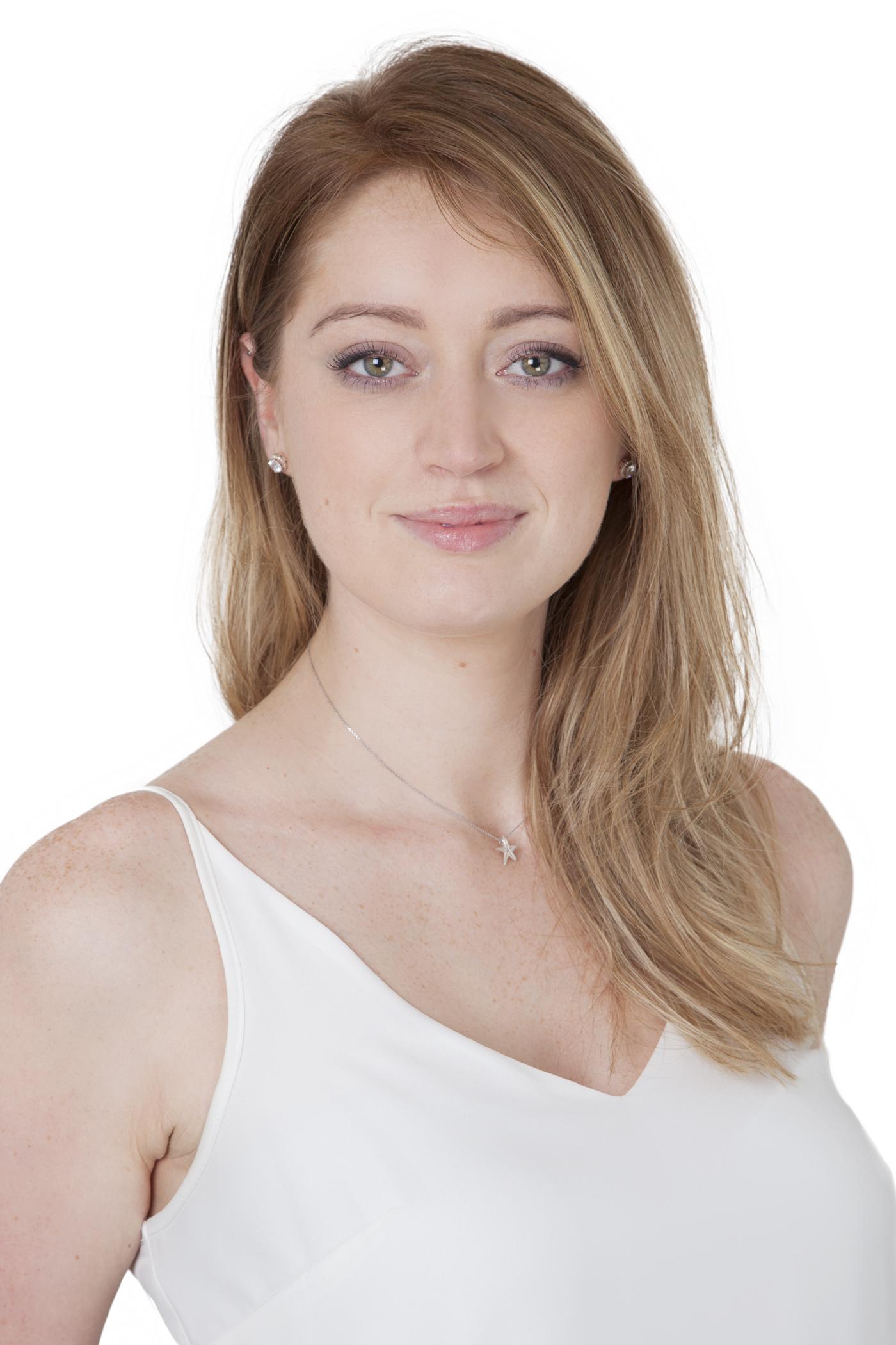 Headshot of woman on white background smiles to camera