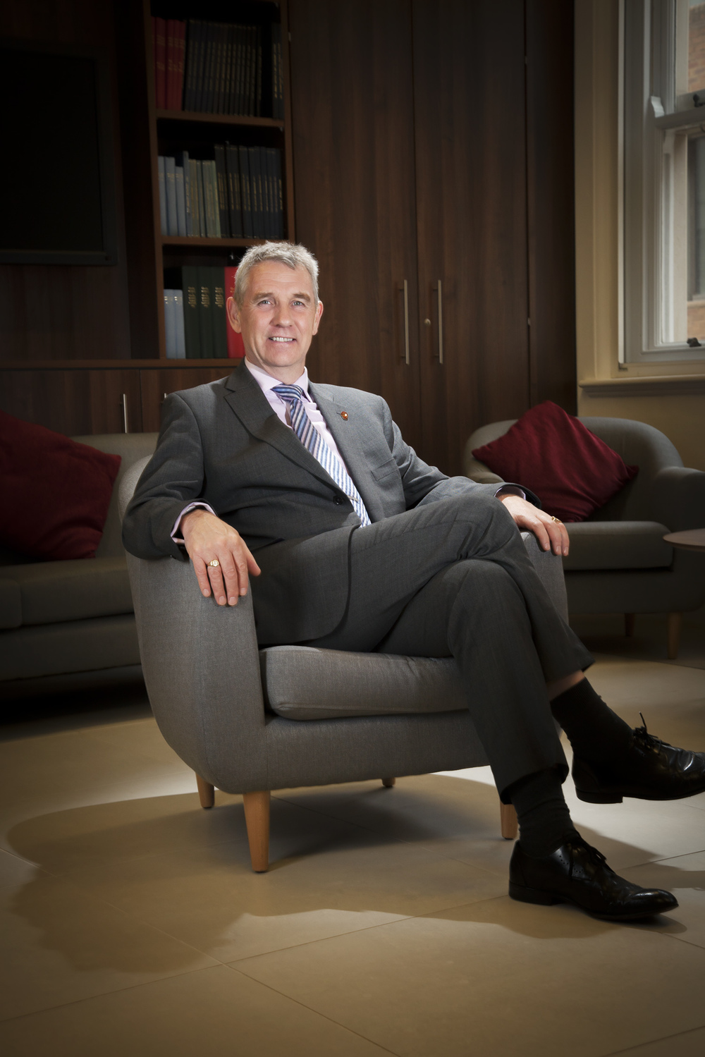 Full length portrait of man in suit sitting on a chair