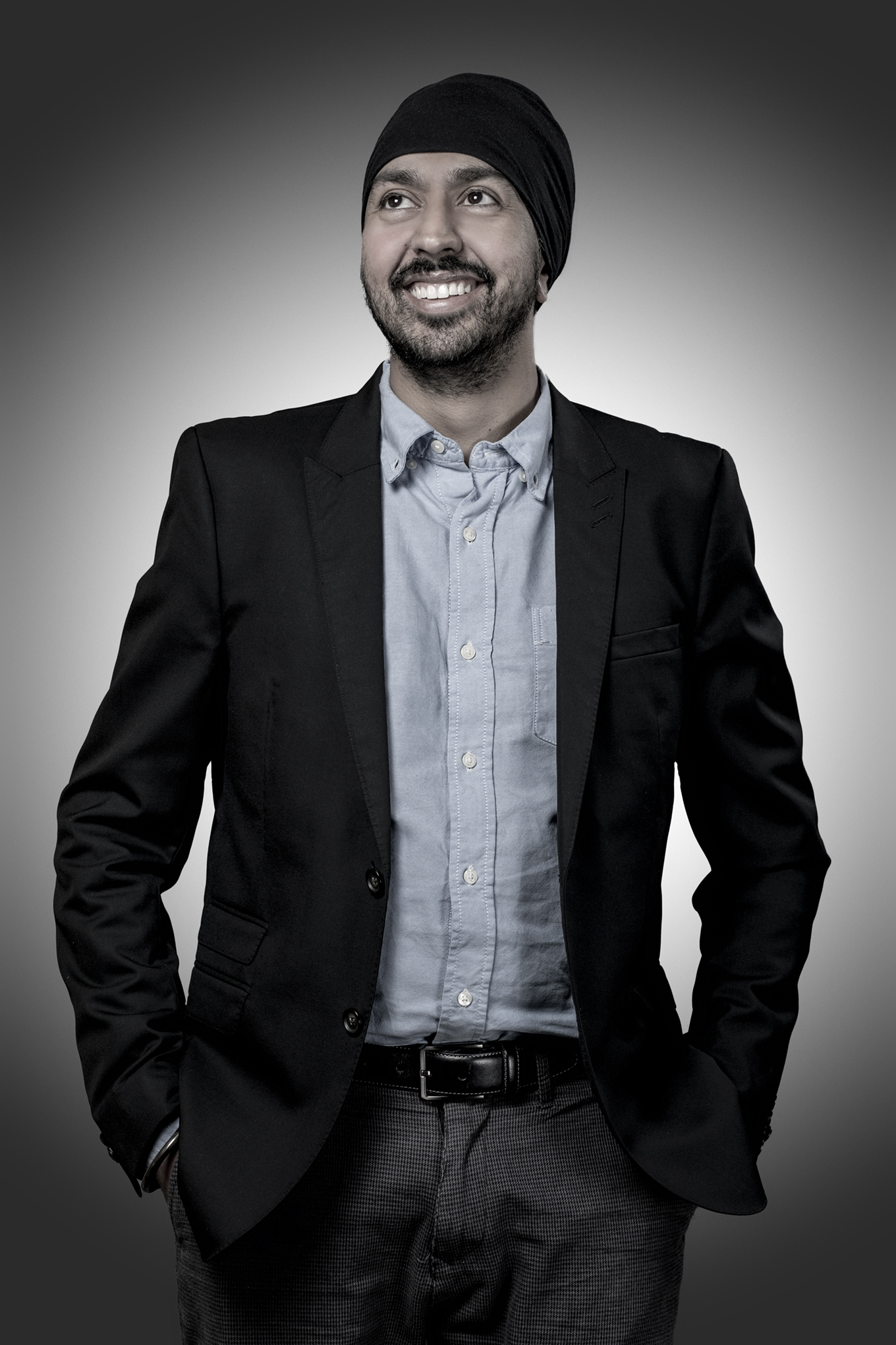Casual business portrait of man in front of graduated grey background