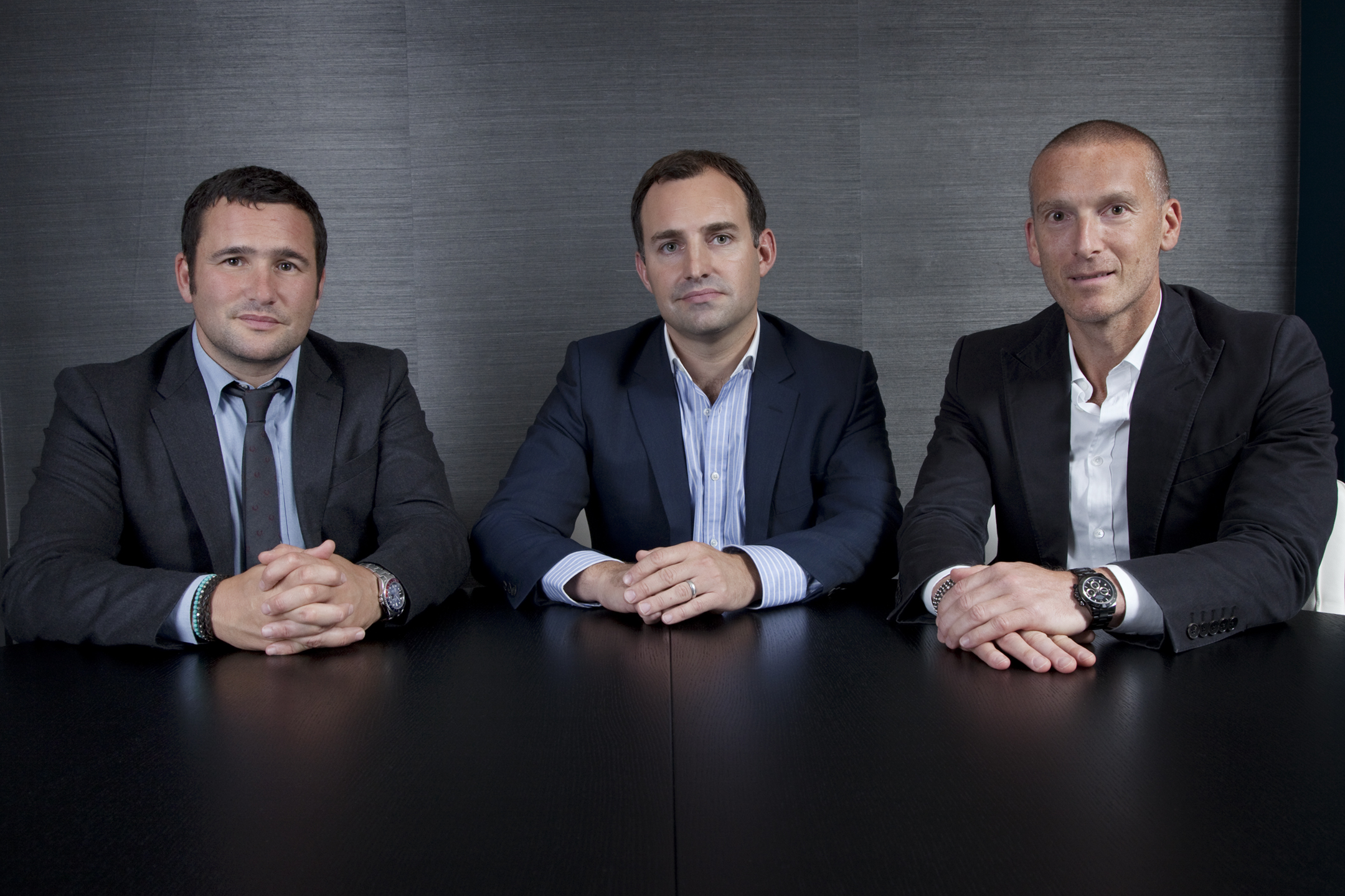 Formal group photograph of three men sitting at a desk