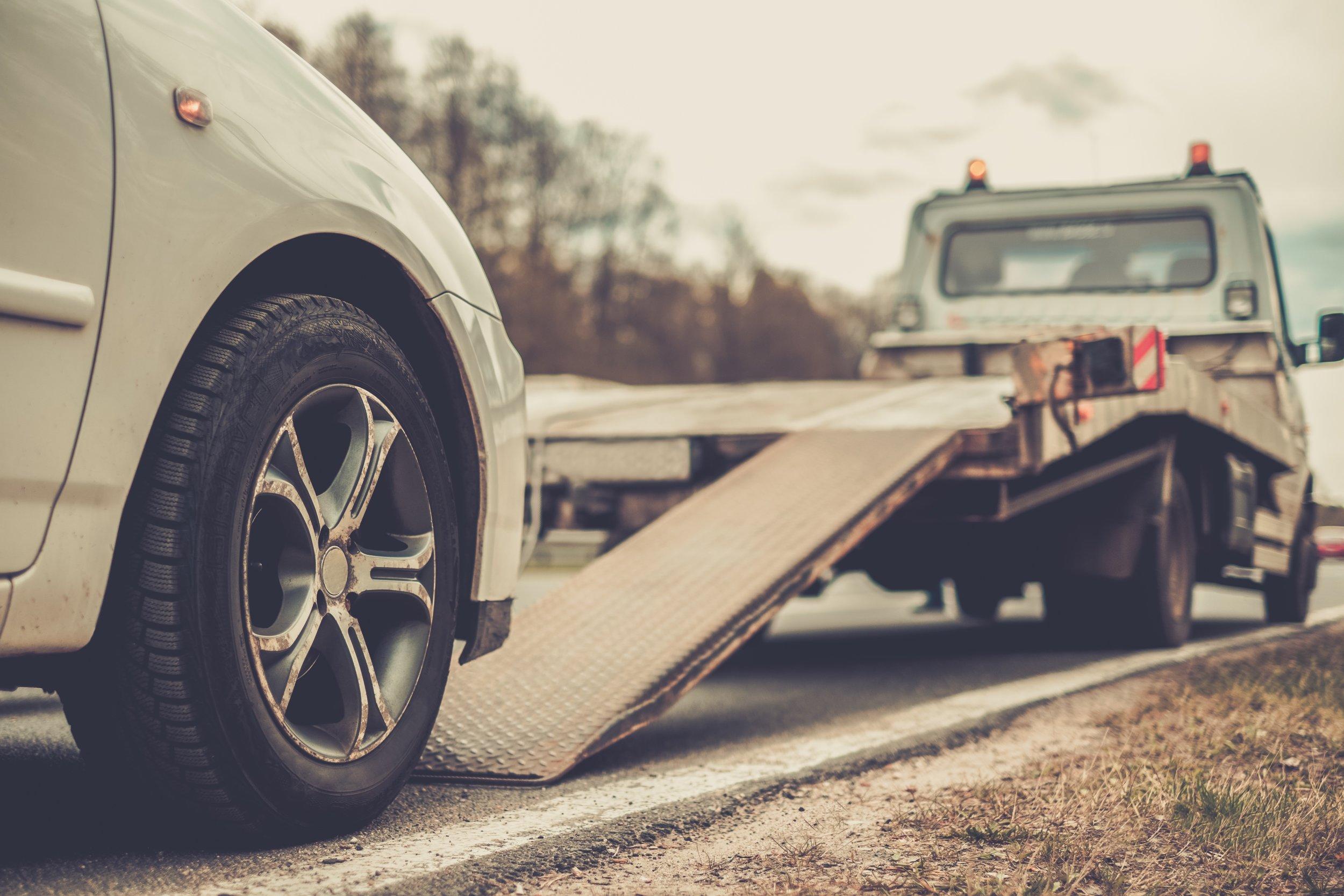 Copy of Loading broken car on a tow truck on a roadside