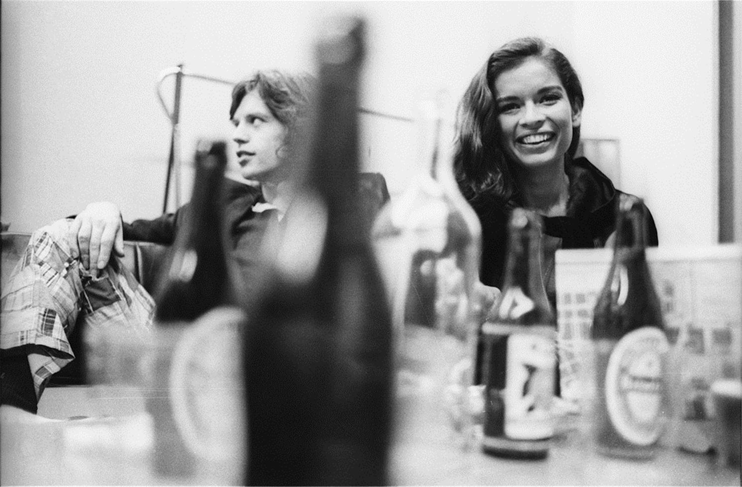 """©  Henry Diltz, 1970   Backstage after a Rolling Stones concert in Amsterdam on October 9, 1970. Henry was trying to photograph Mick through the bottles on the table so he wouldn't notice.  """"Some girl next to him kept watching me and smiling, which made it hard for me to hide what I was doing. Later I learned she was his girlfriend, Bianca."""" -Henry Diltz"""