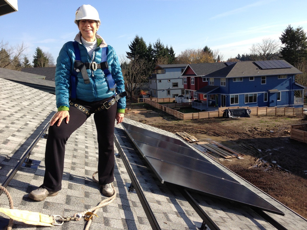 Margie Harris standing on her rooftop with her solar modules.