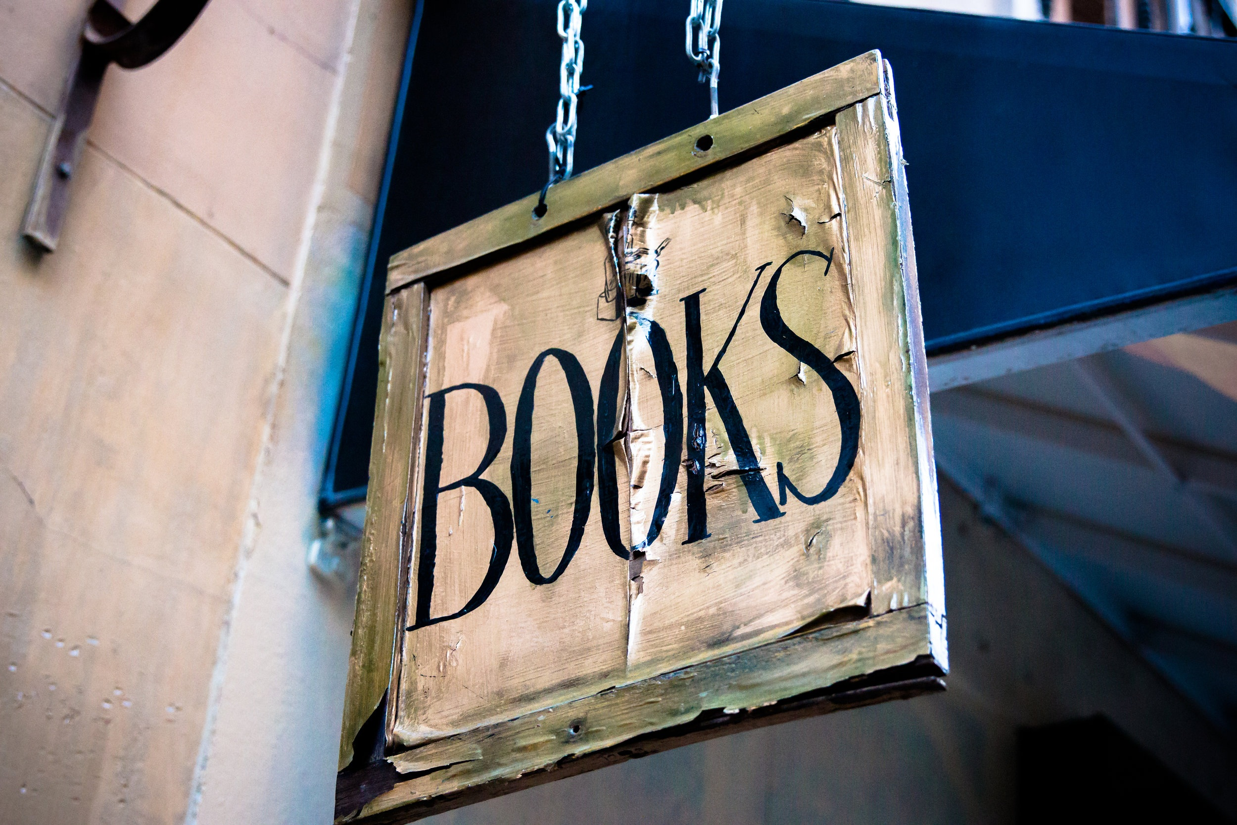 "{Image of a wooden bookstore sign that reads ""BOOKS�}"