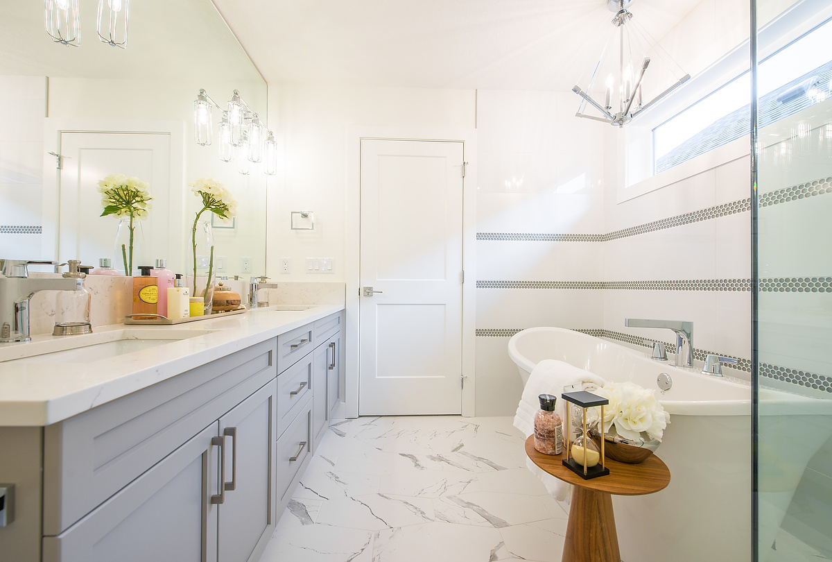 Bright whites, marble, and minimal wood create a bathroom that feels clean and fresh - a great place to start your morning routine.