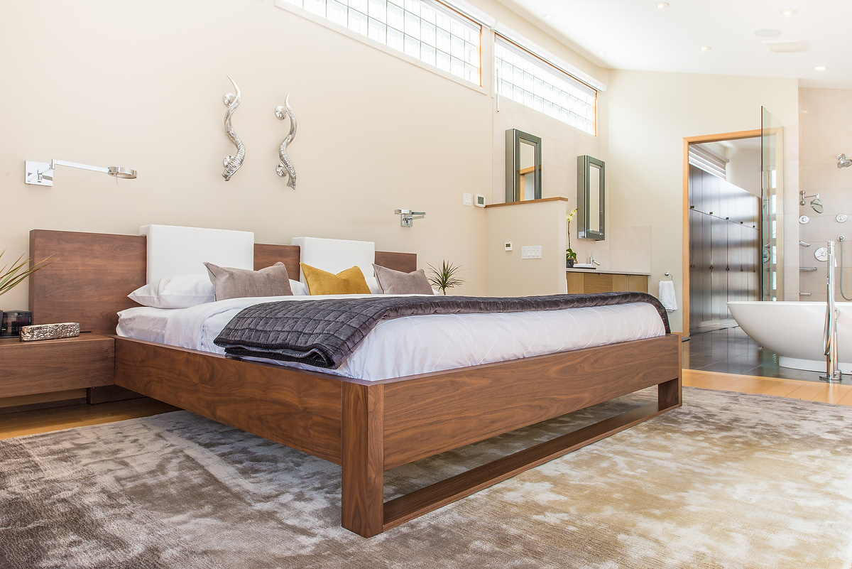 This large, solid wood bed provides a visual anchor in this open style master bedroom.