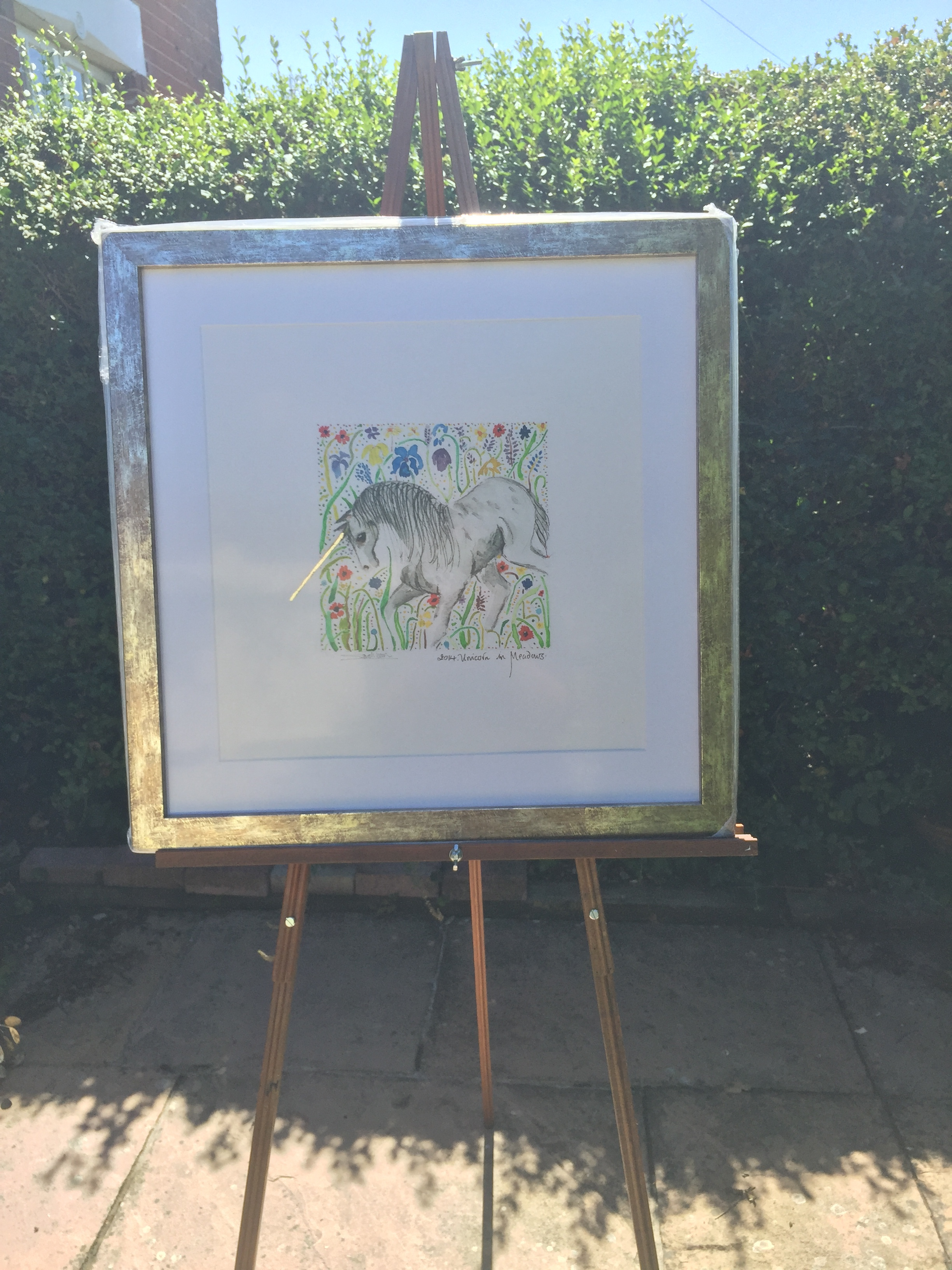 Framed edition of Unicorn Print. In full sunshine and gold frame, the light catches his horn that is finished in gold leaf.