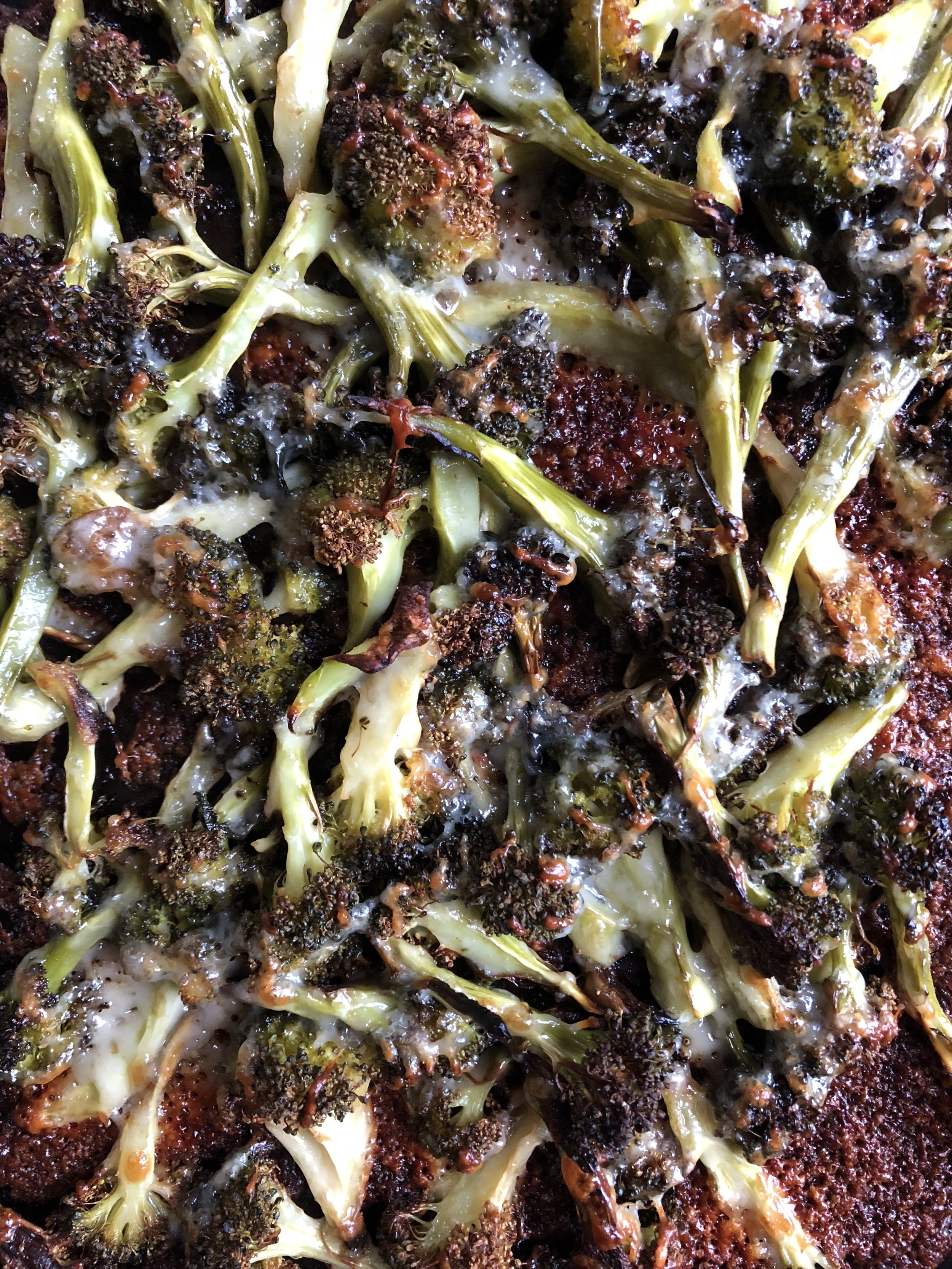 Roasted broccoli topped with parmesan cheese and browned