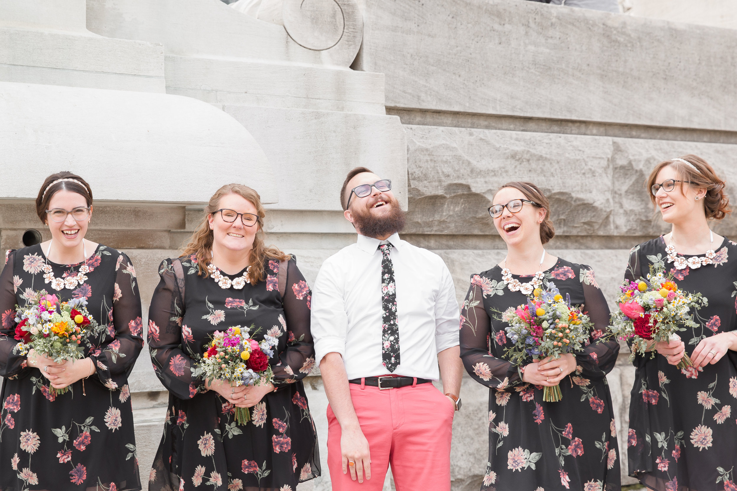 groom laughing with bridesmaids in downtown indianapolis