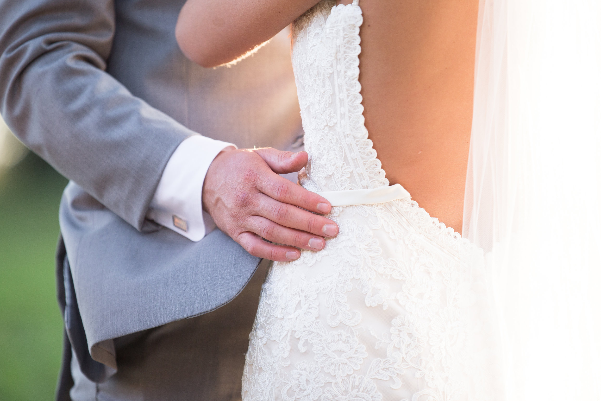close up of groom's hand on bride's waist