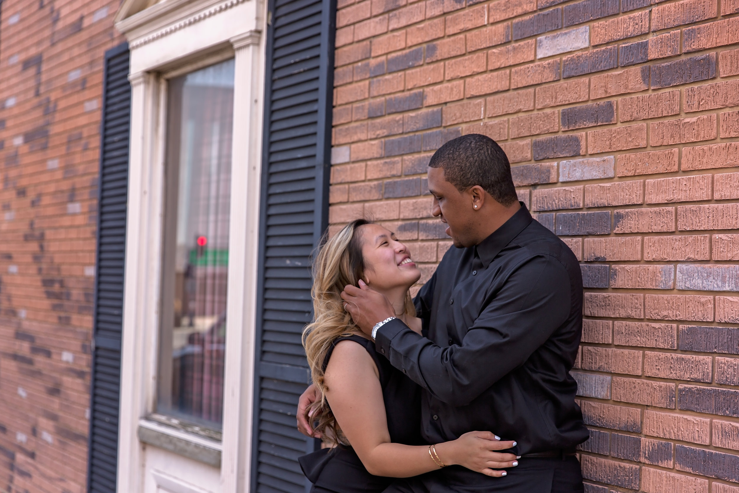 couple leaning up against brick wall embracing