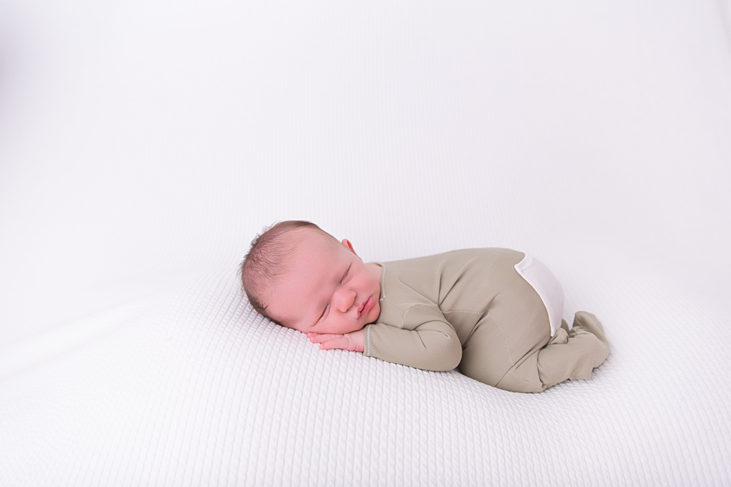 newborn baby boy in outfit curled up sleeping