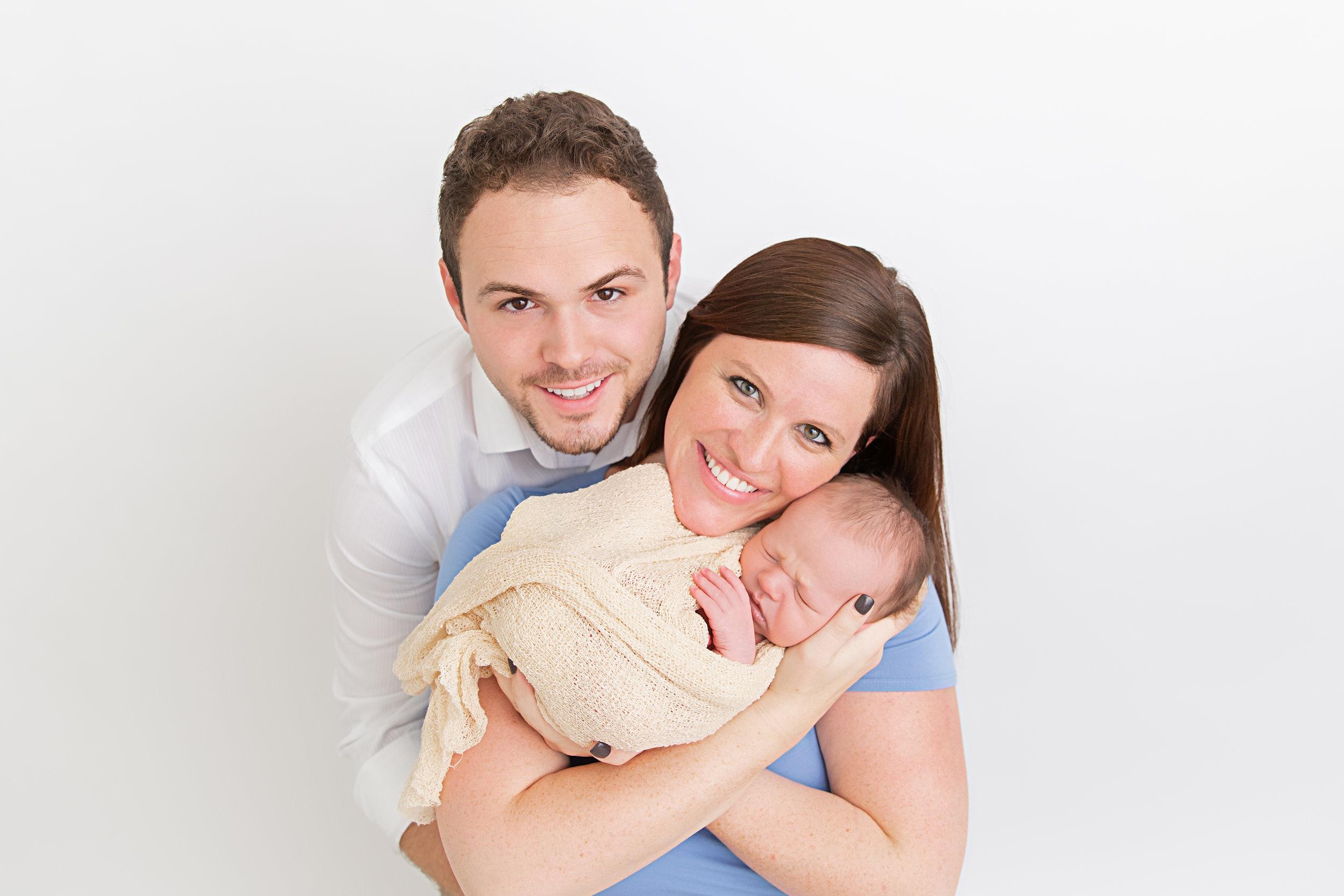 new parents and sleeping newborn baby boy