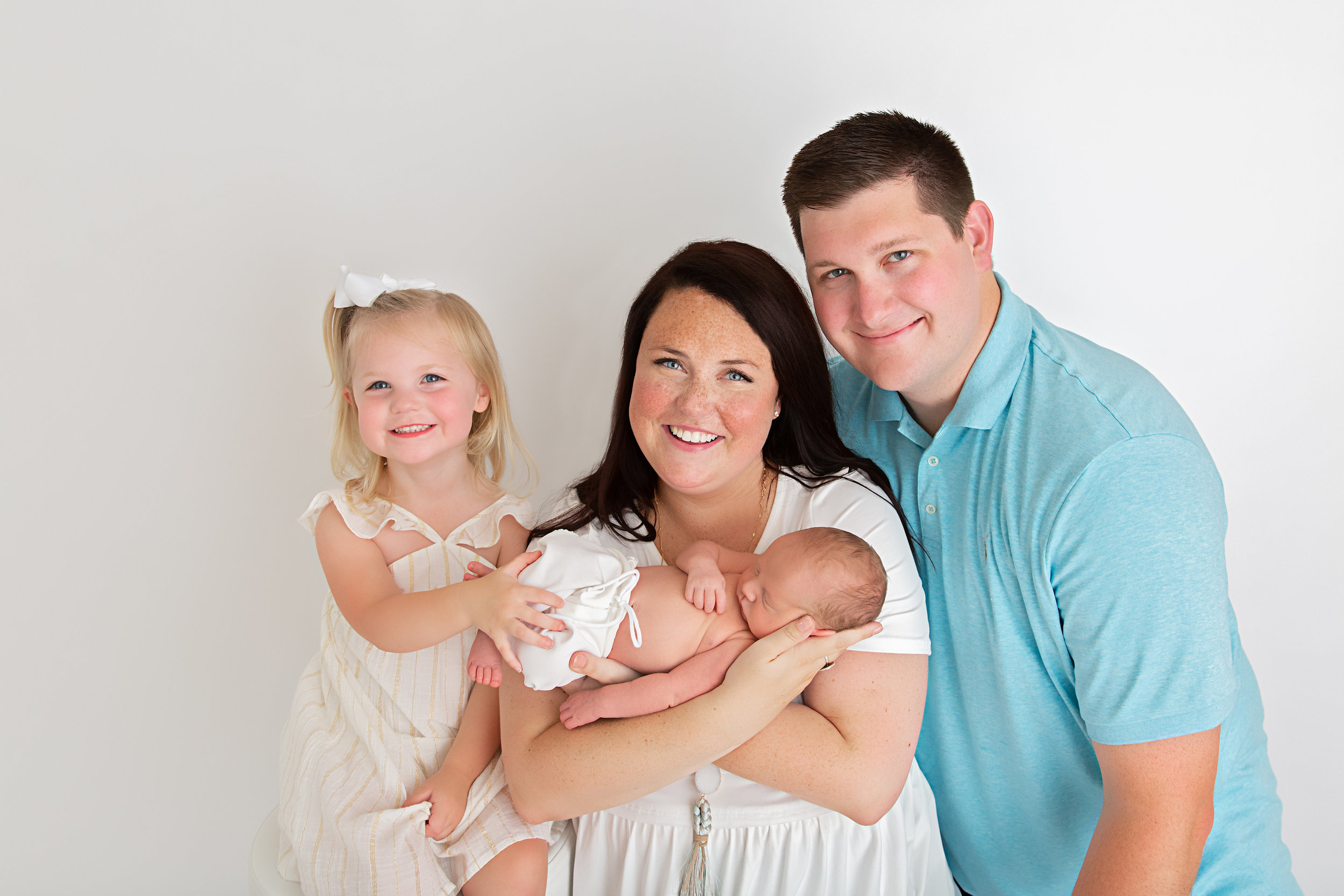 new family of four with newborn baby