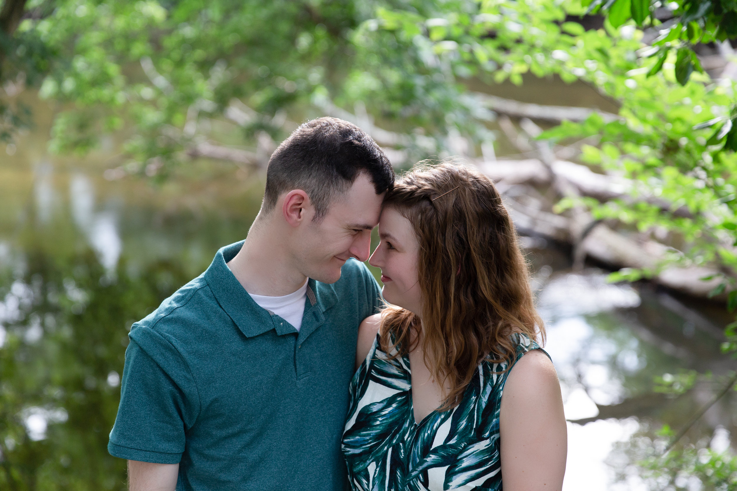 engaged couple with foreheads touching in park area