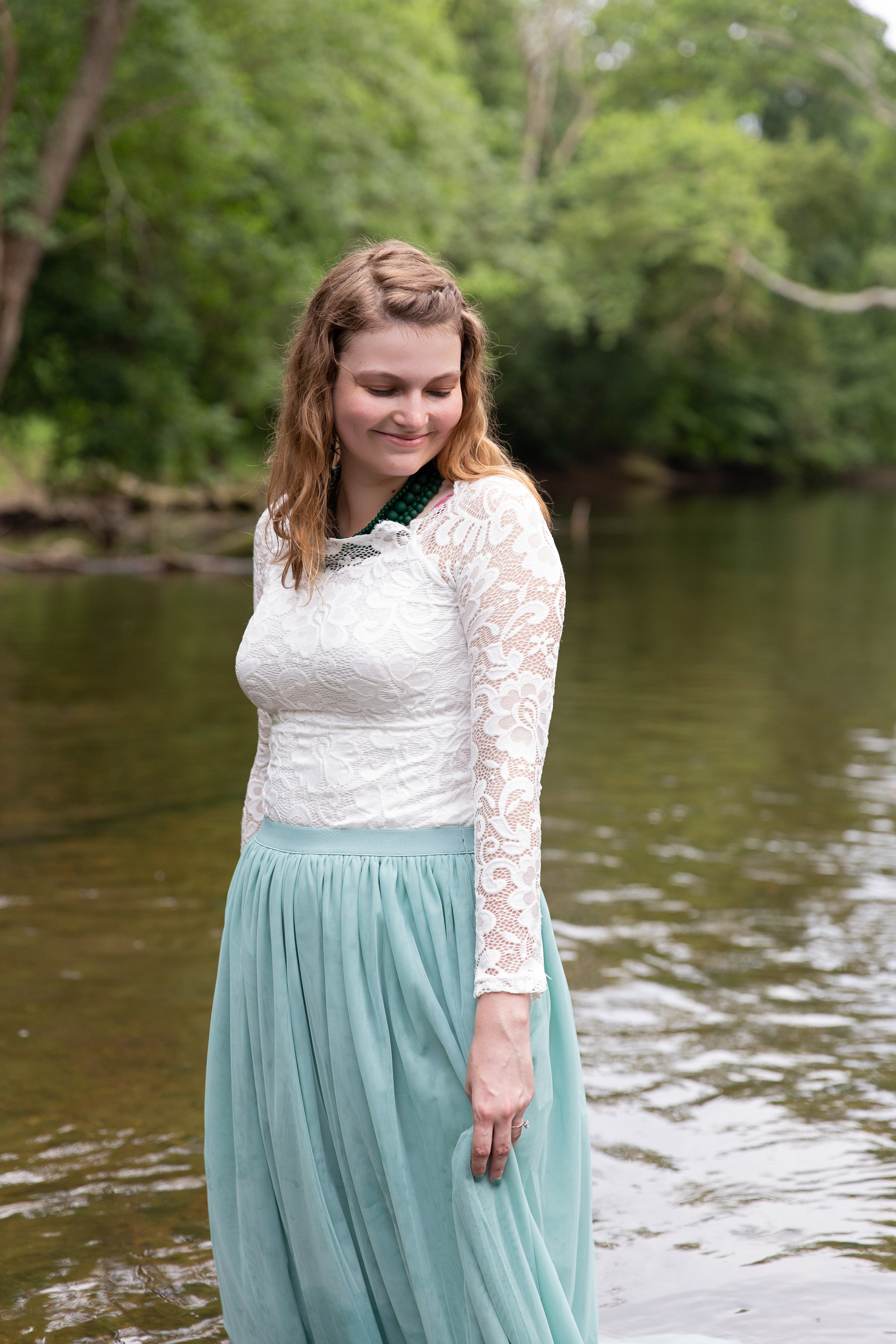 bride to be smiling and looking down while standing in creek