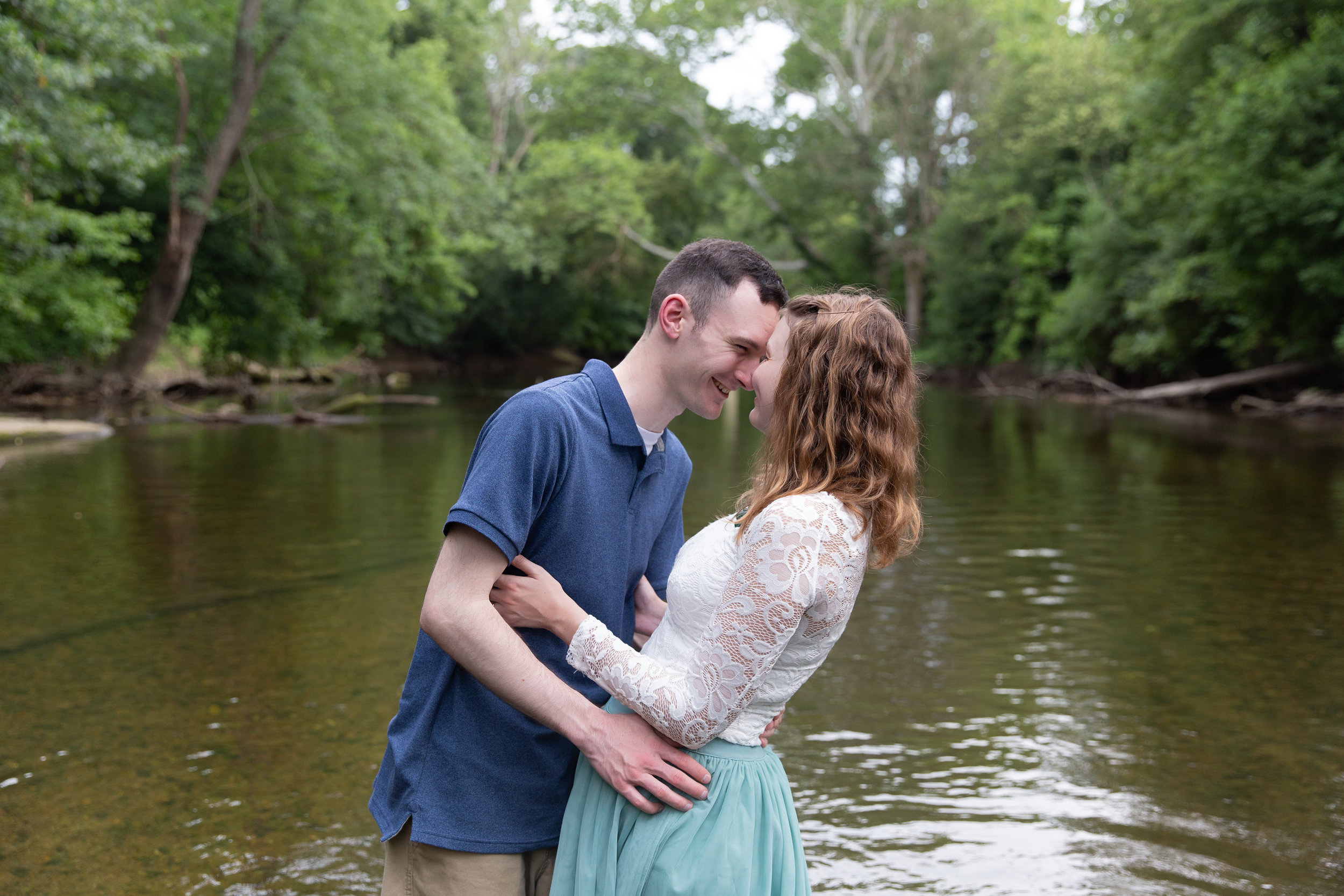 engaged couple leaning into each other while wading into creek