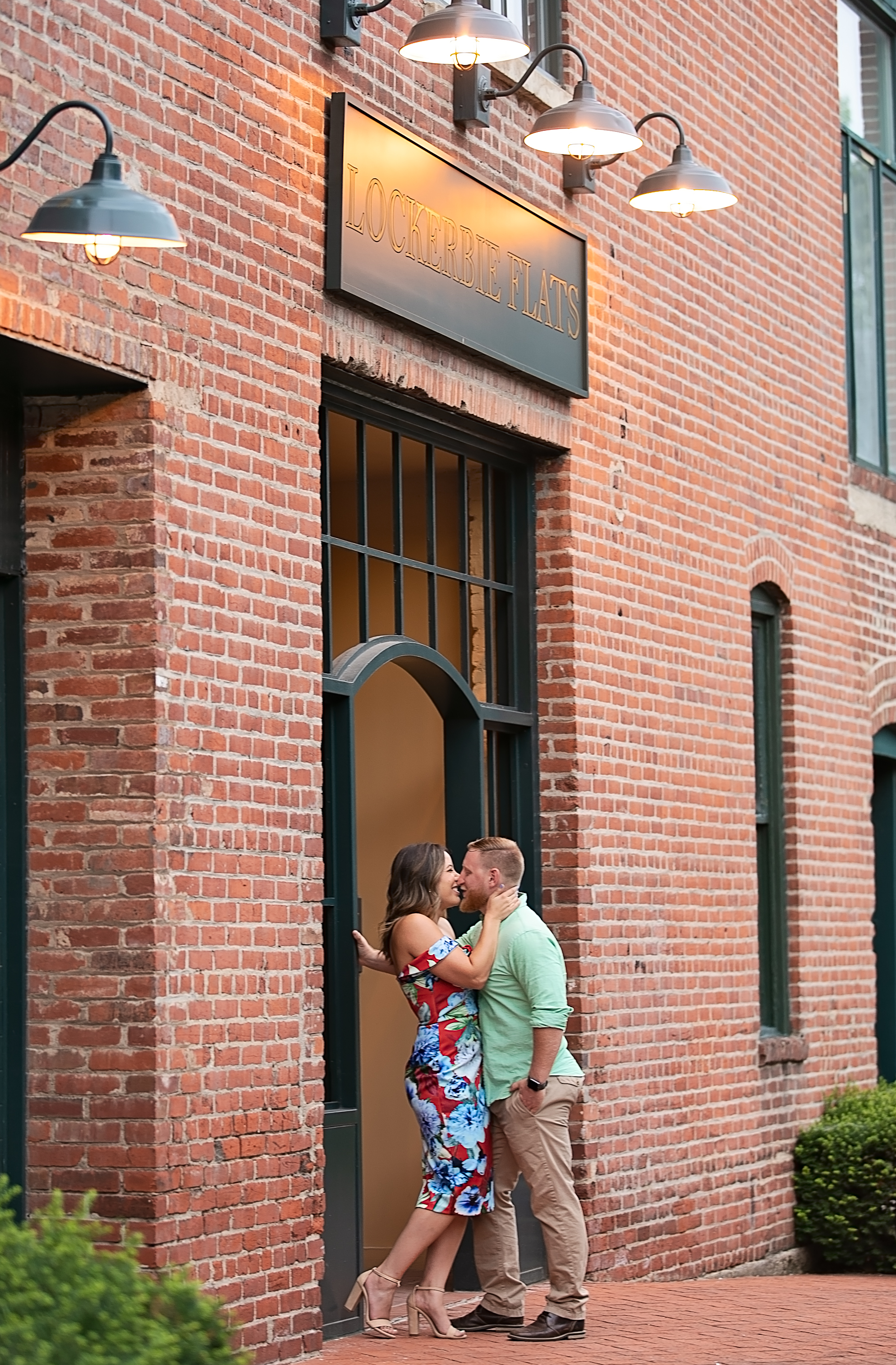 engaged couple kissing on church steps