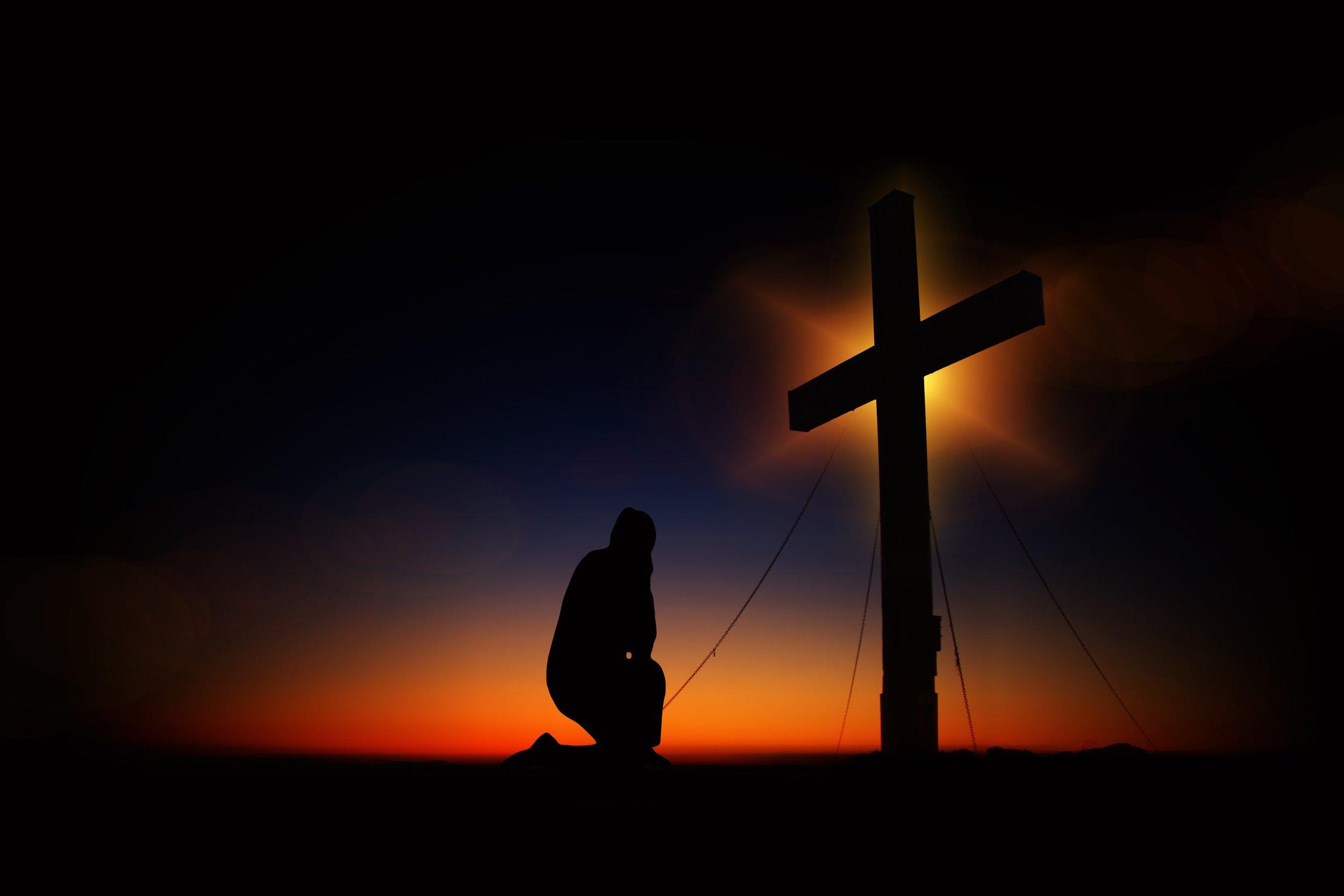 Man Kneeling Beneath the Cross of Jesus