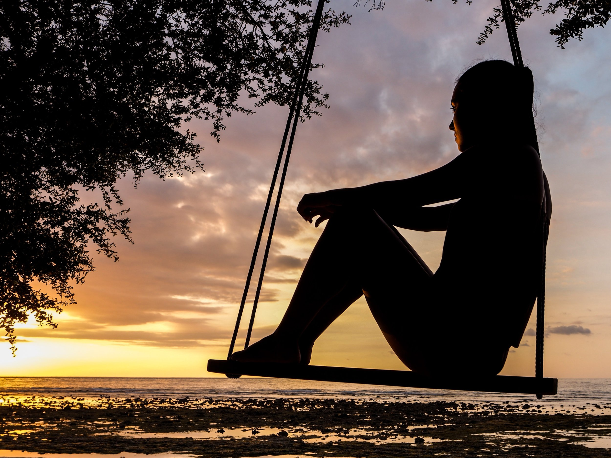Young Woman on Swing at Sunset in Contemplation