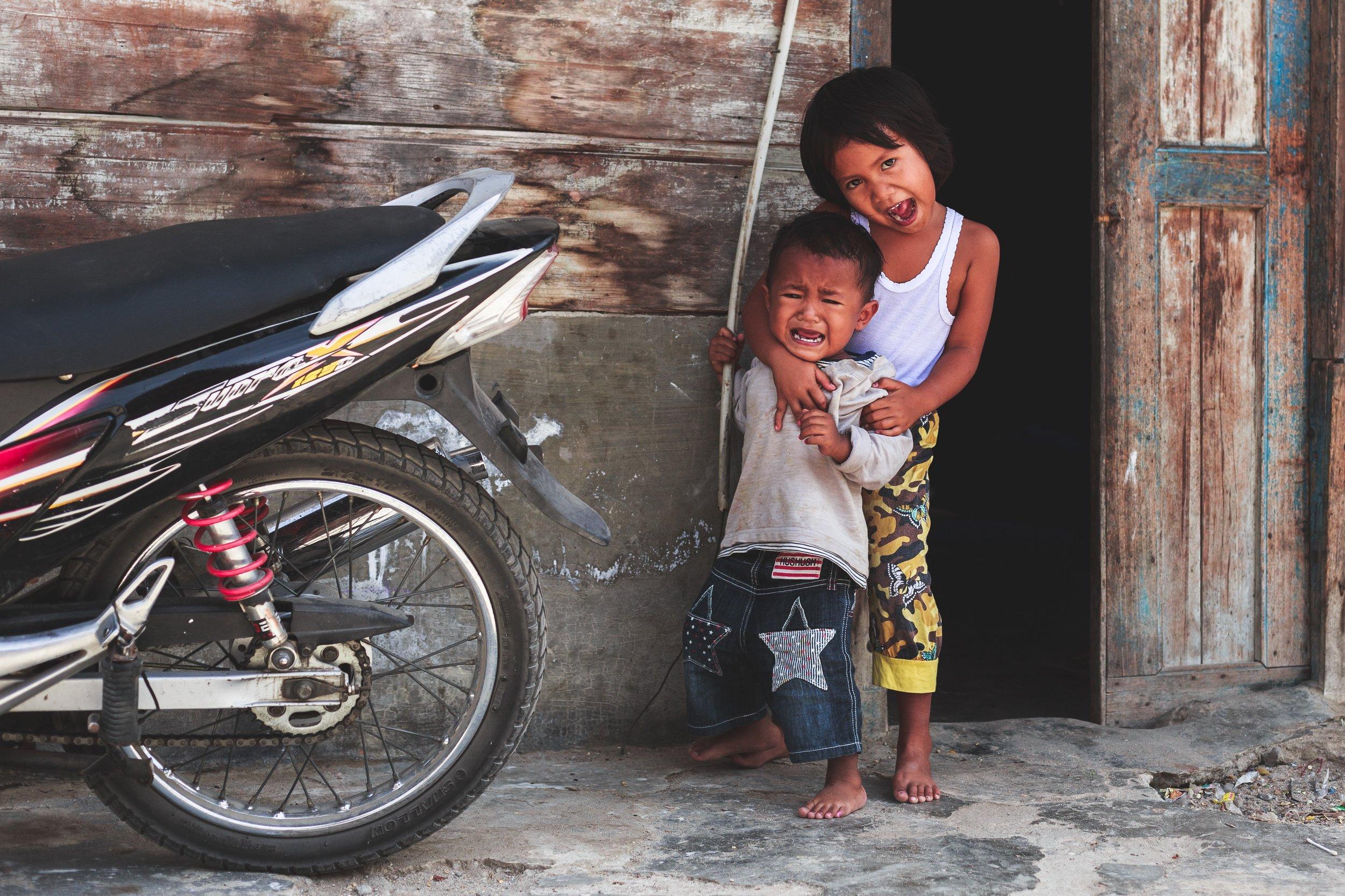 Siblings on Street Standing by Motorcyle