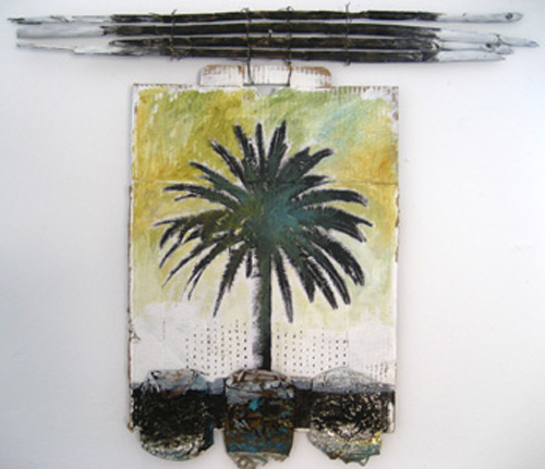 Palm tree finds it's place on cardboard with crushed cans and seaside fencing.