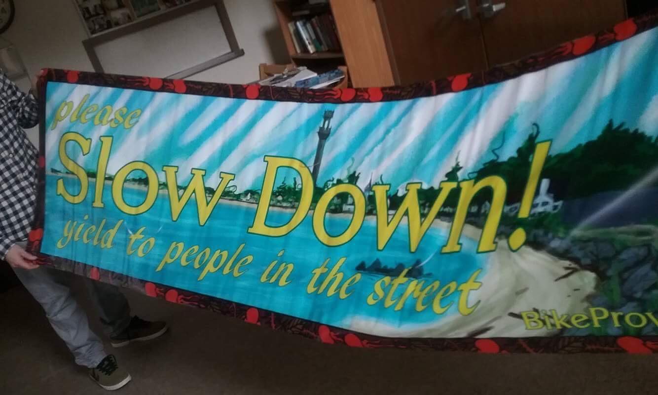 """Slow Down"" bike safety street banner."