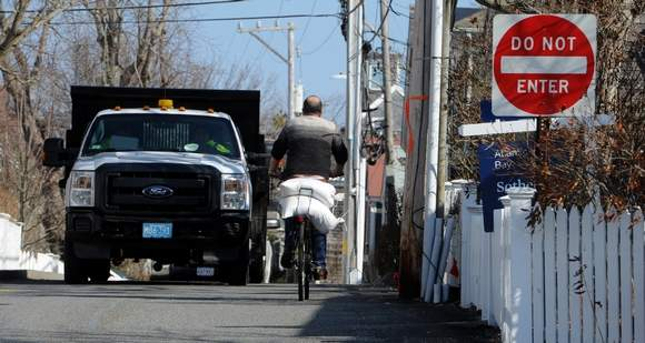 Carrying sandbags on a bike in preparation for a coming nor'easter (Photo: Steve Heaslip/Cape Cod Times)