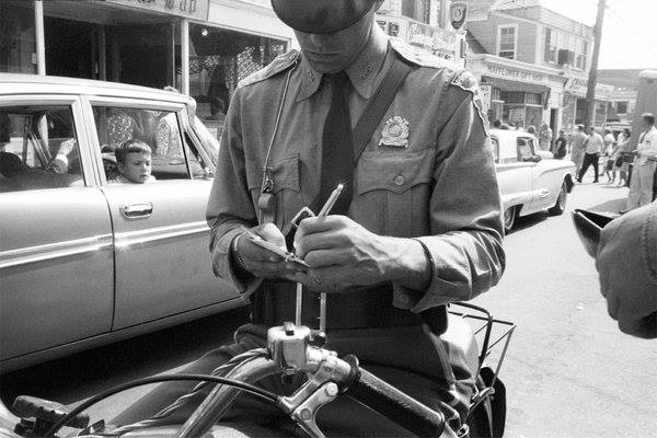 Police officer on bike writing parking ticket 1962 outside Old Colony on Commercial St - My Grandfather's Provincetown - Lisa King