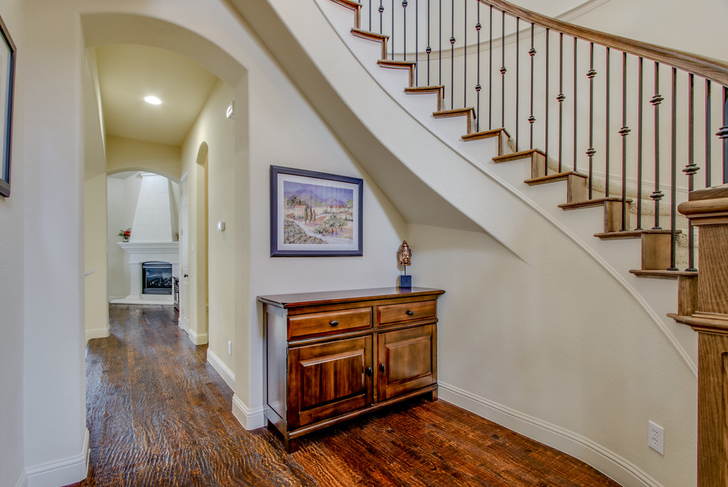 Foyer w handscraped wood floors, spiral stairs & tall ceilings.