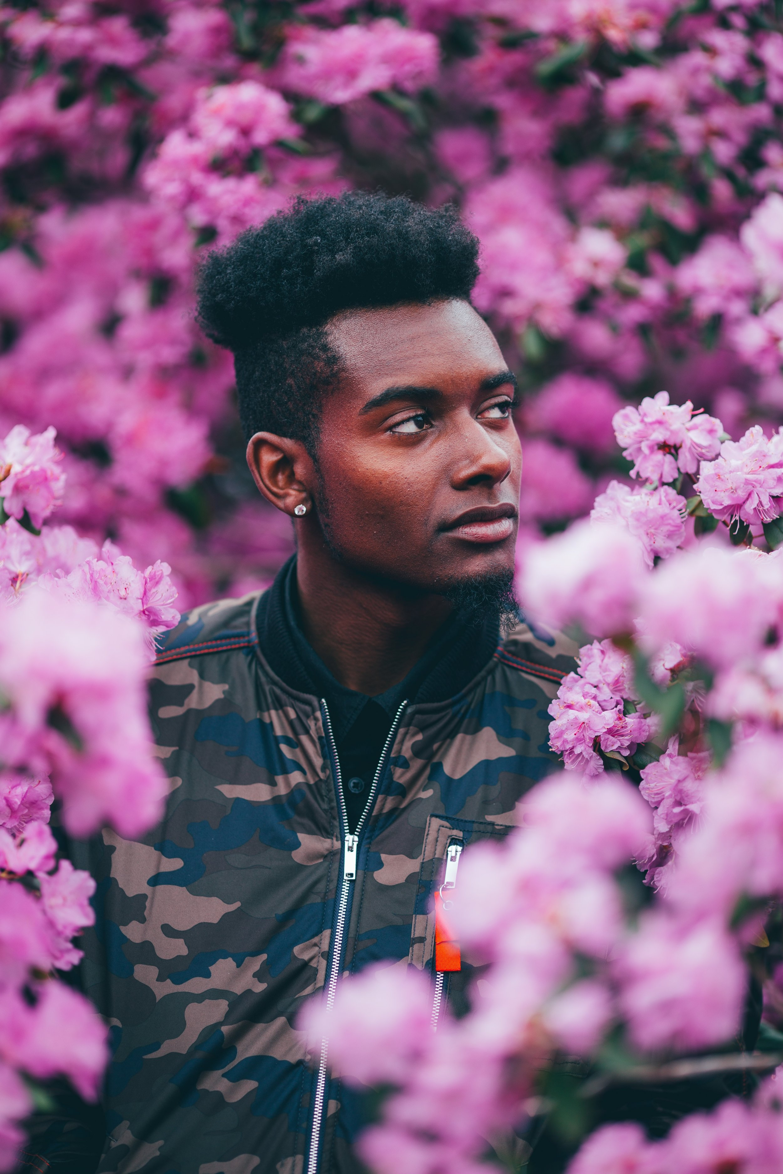 black-man-surrounded-by-pink-flowers-puckn-khaos-article