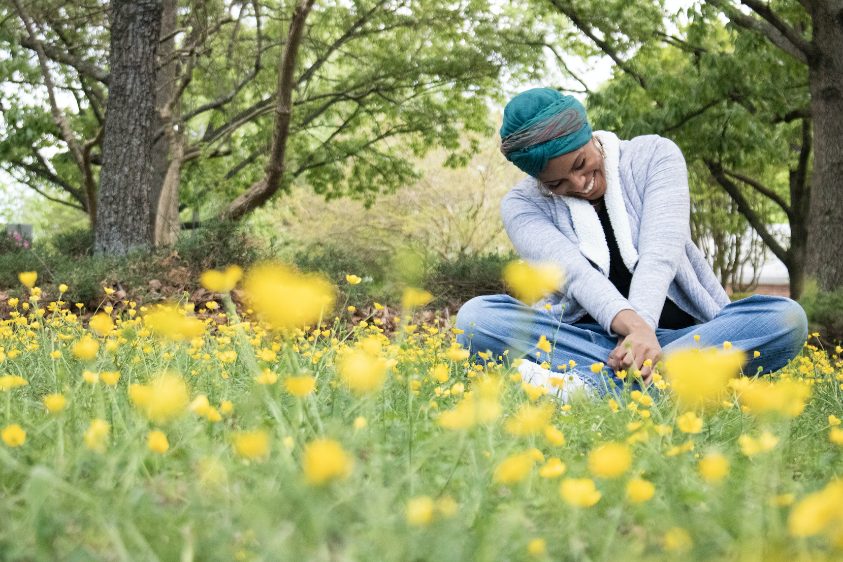 black-girl-with-headwrap-sitting-in-a-bed-of-yellow-flowers-puckn-khaos