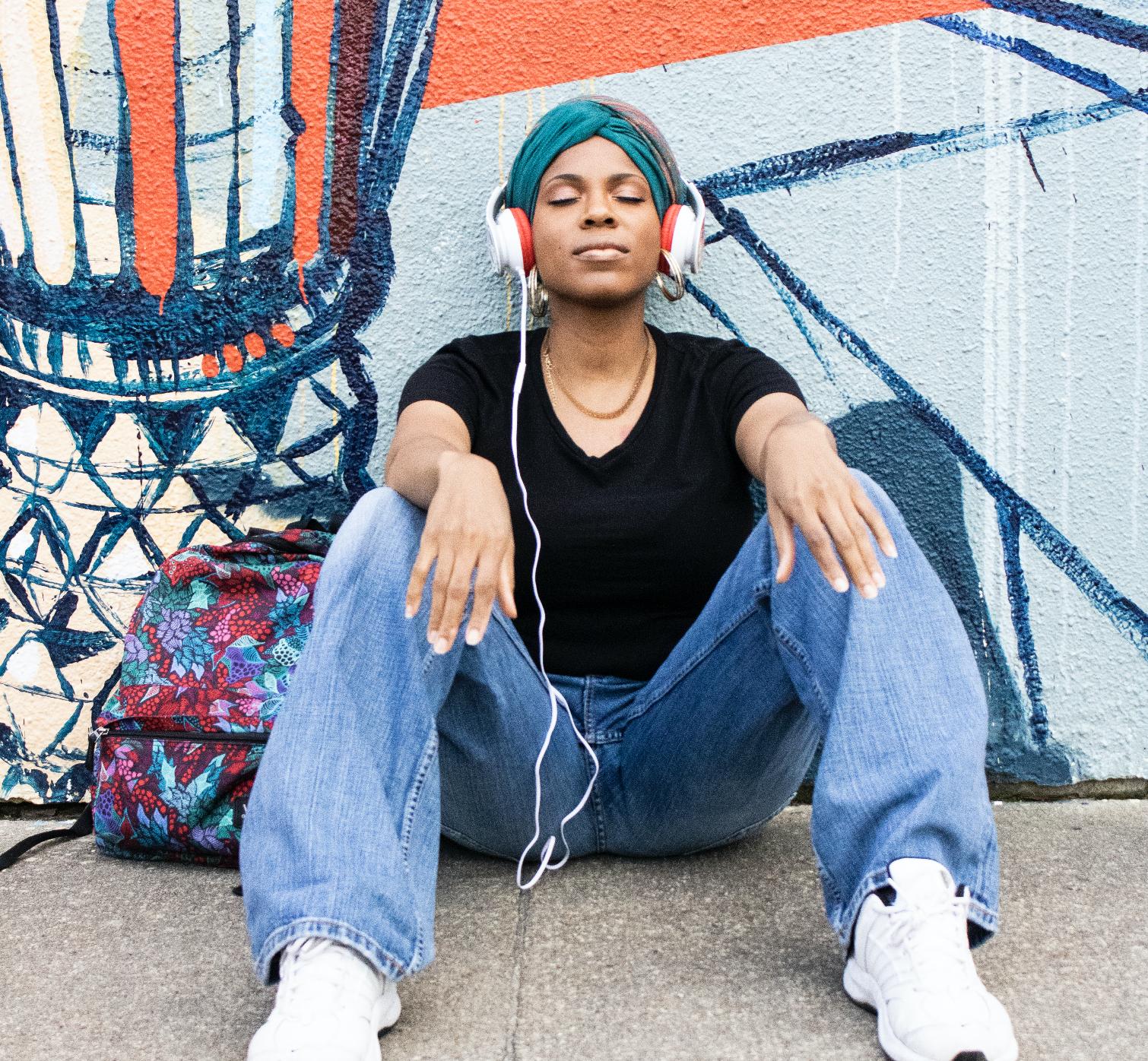 black-girl-with-headwrap-sitting-on-sidewalk-puckn-khaos