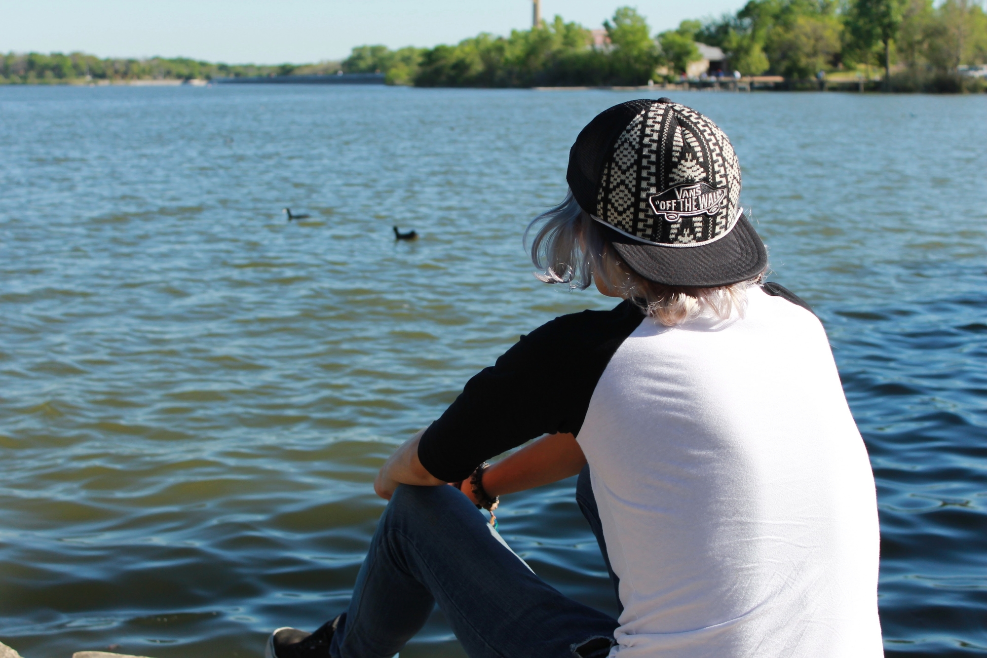 photo of influencer from behind staring at white rock lake with ducks