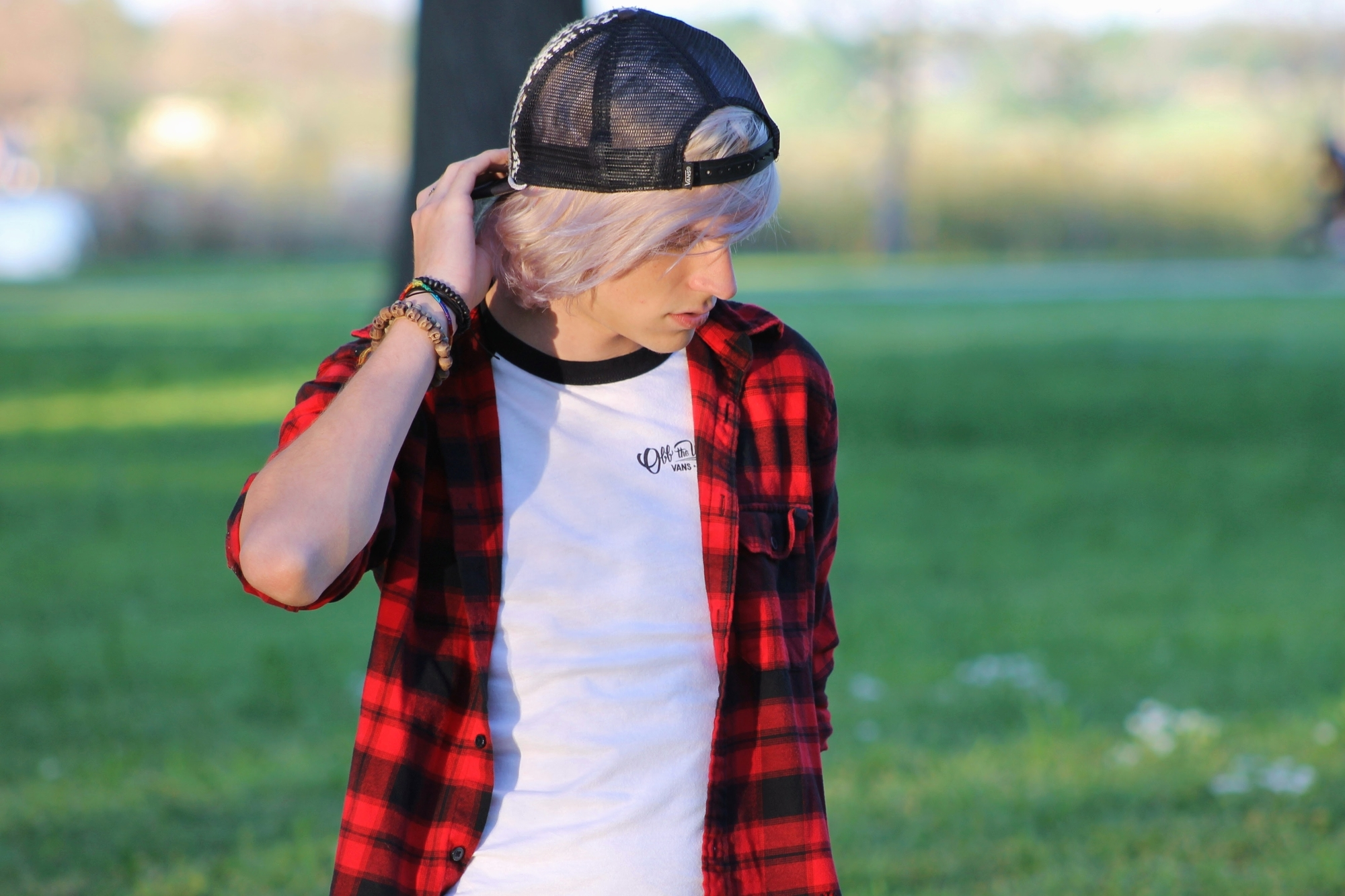 influencer in red plaid shirt touching cap lightly