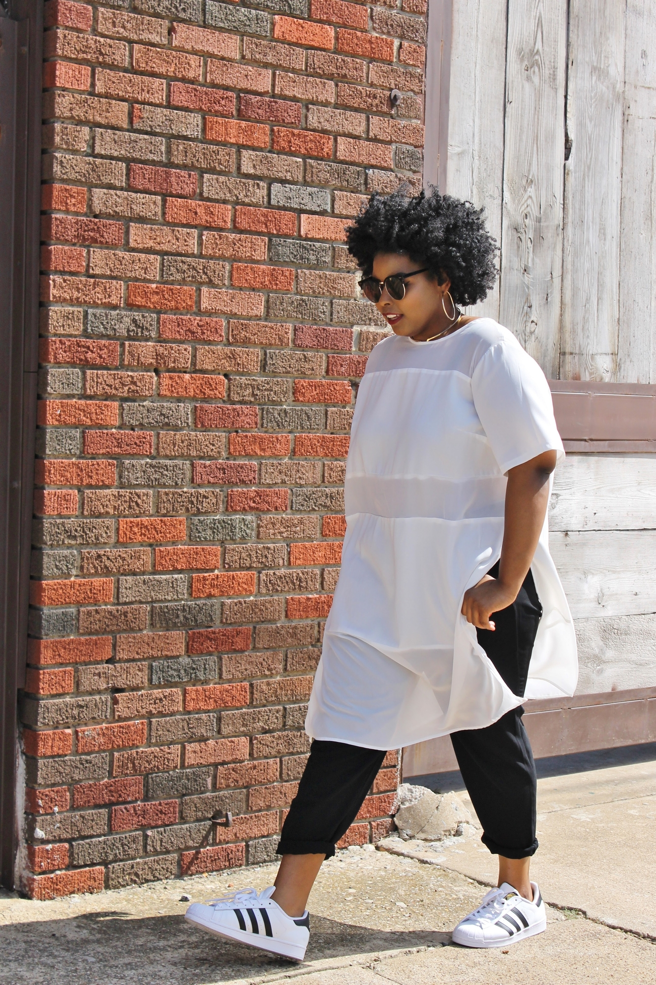 fashion influencer walking by brick wall