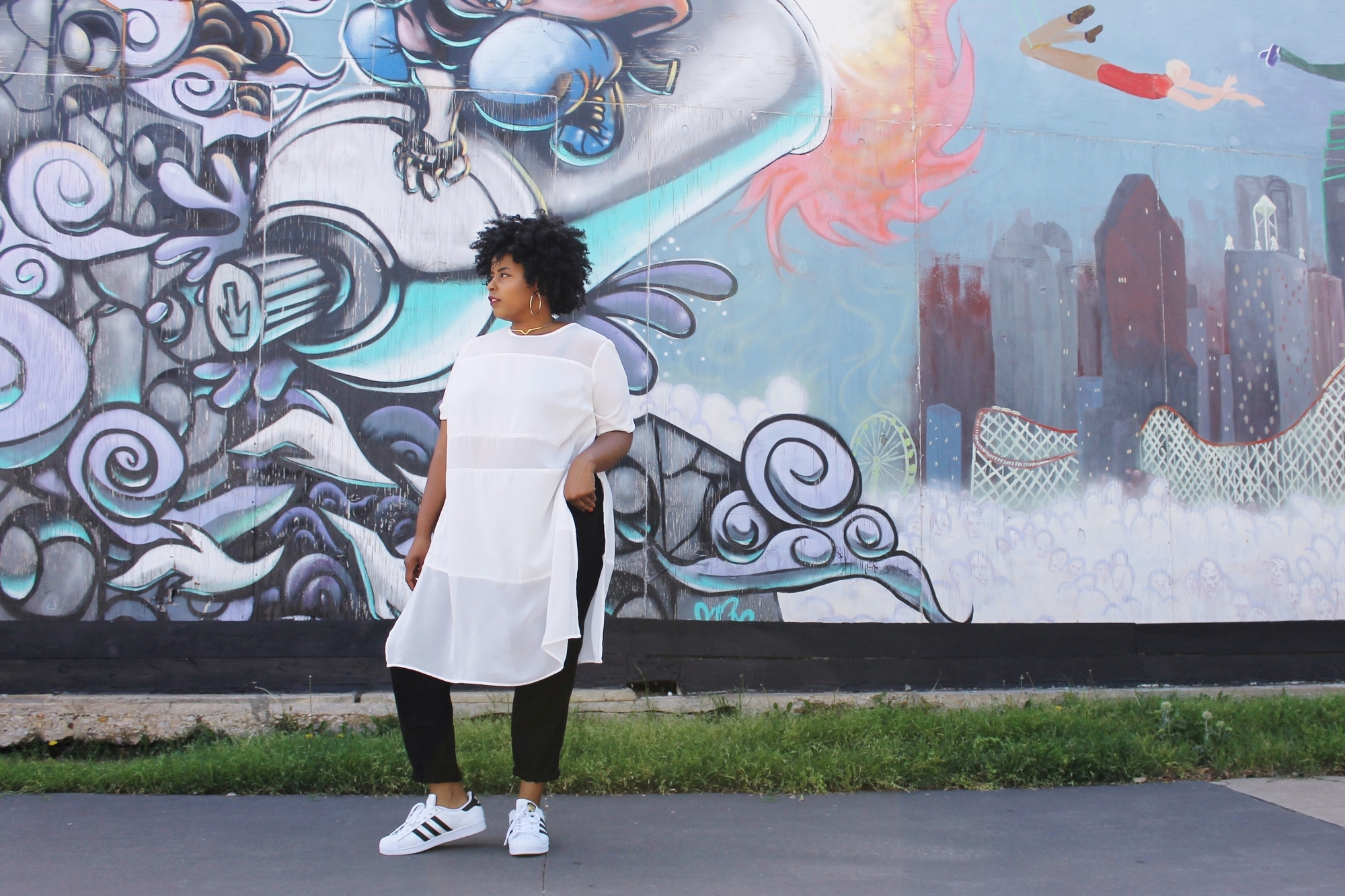 woman in front of graffiti wall posing in outfit