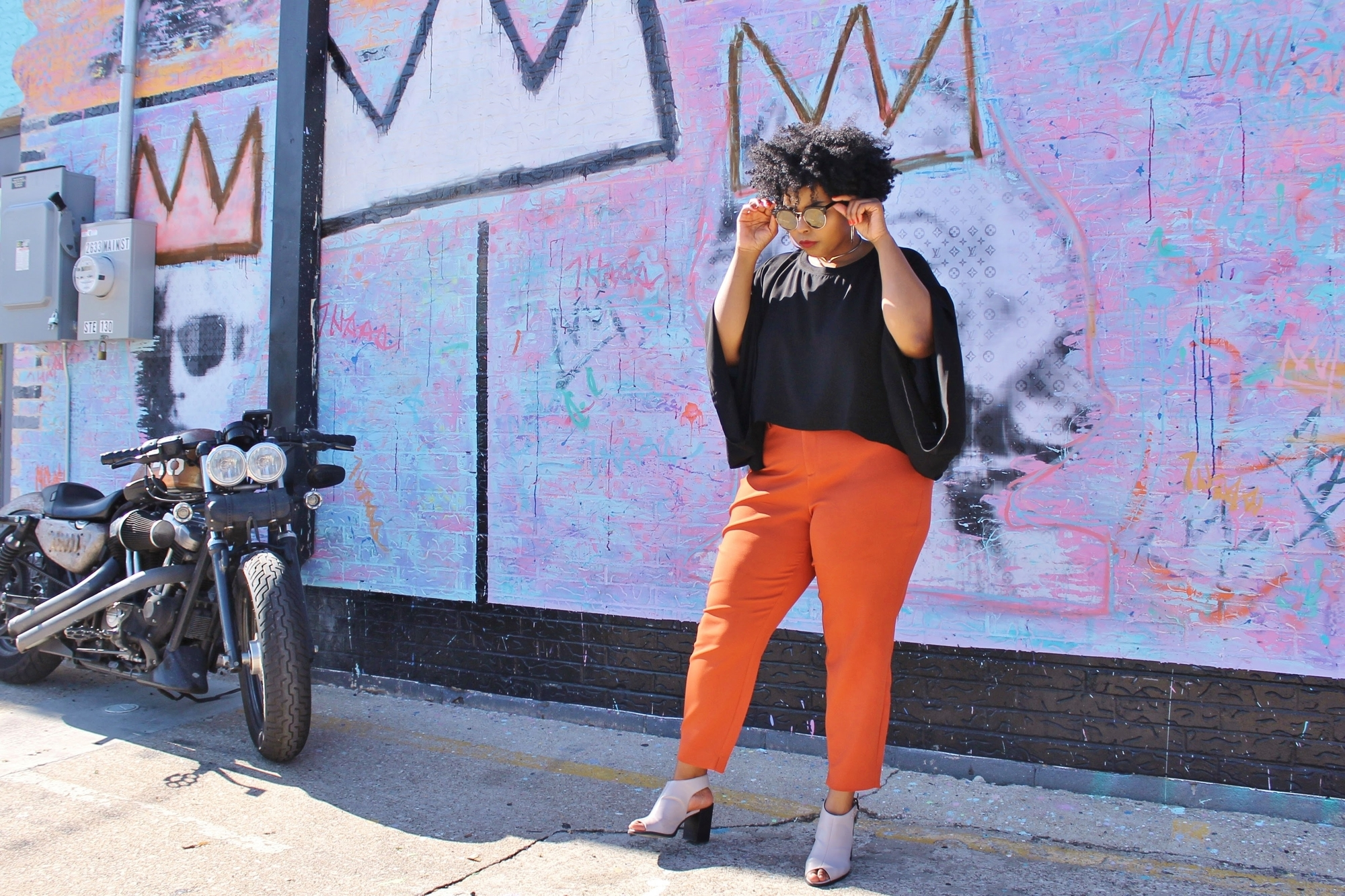 woman in orange pants and boots next to motorcycle