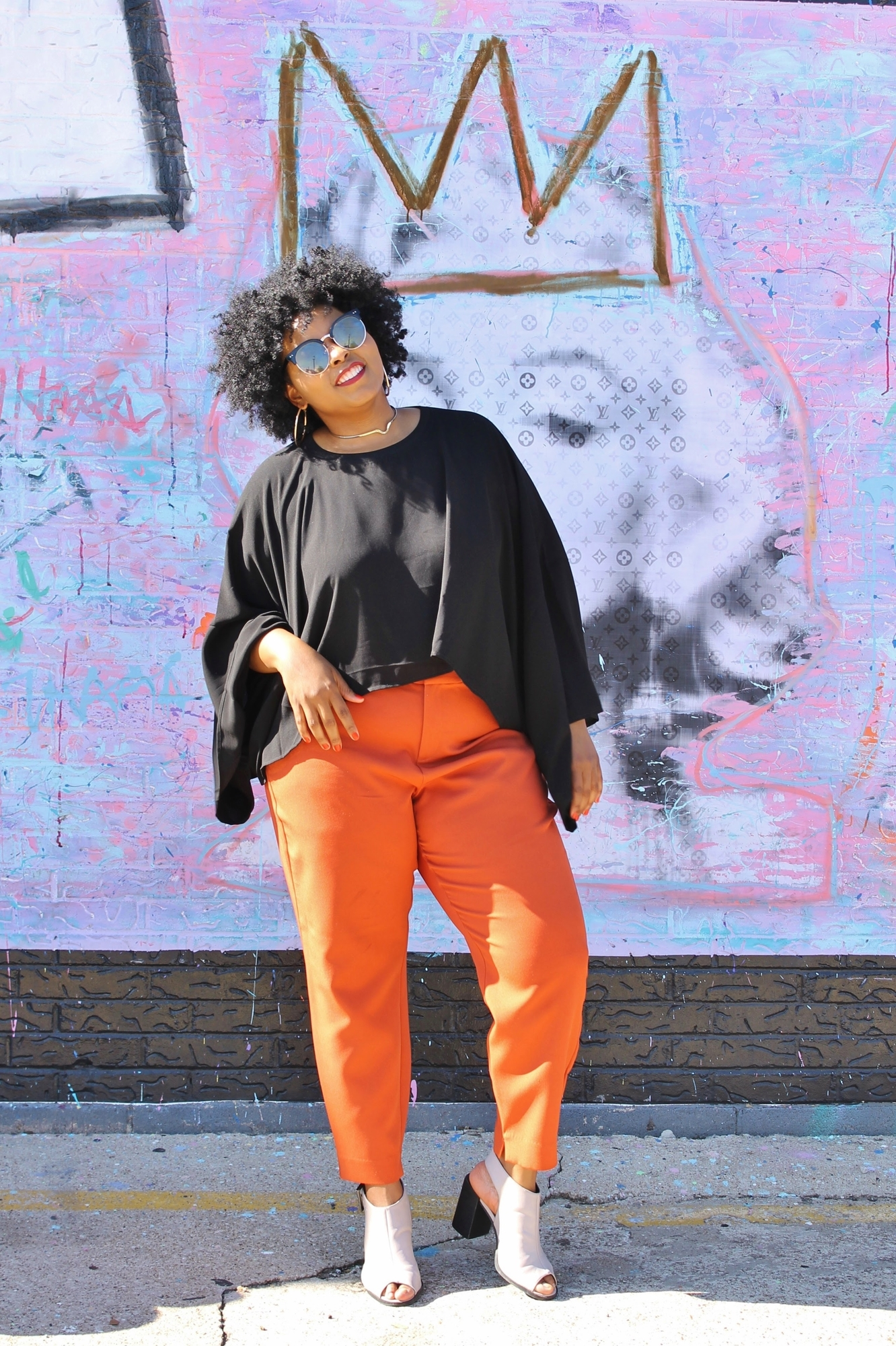 business coach in black flowy shirt and orange pants