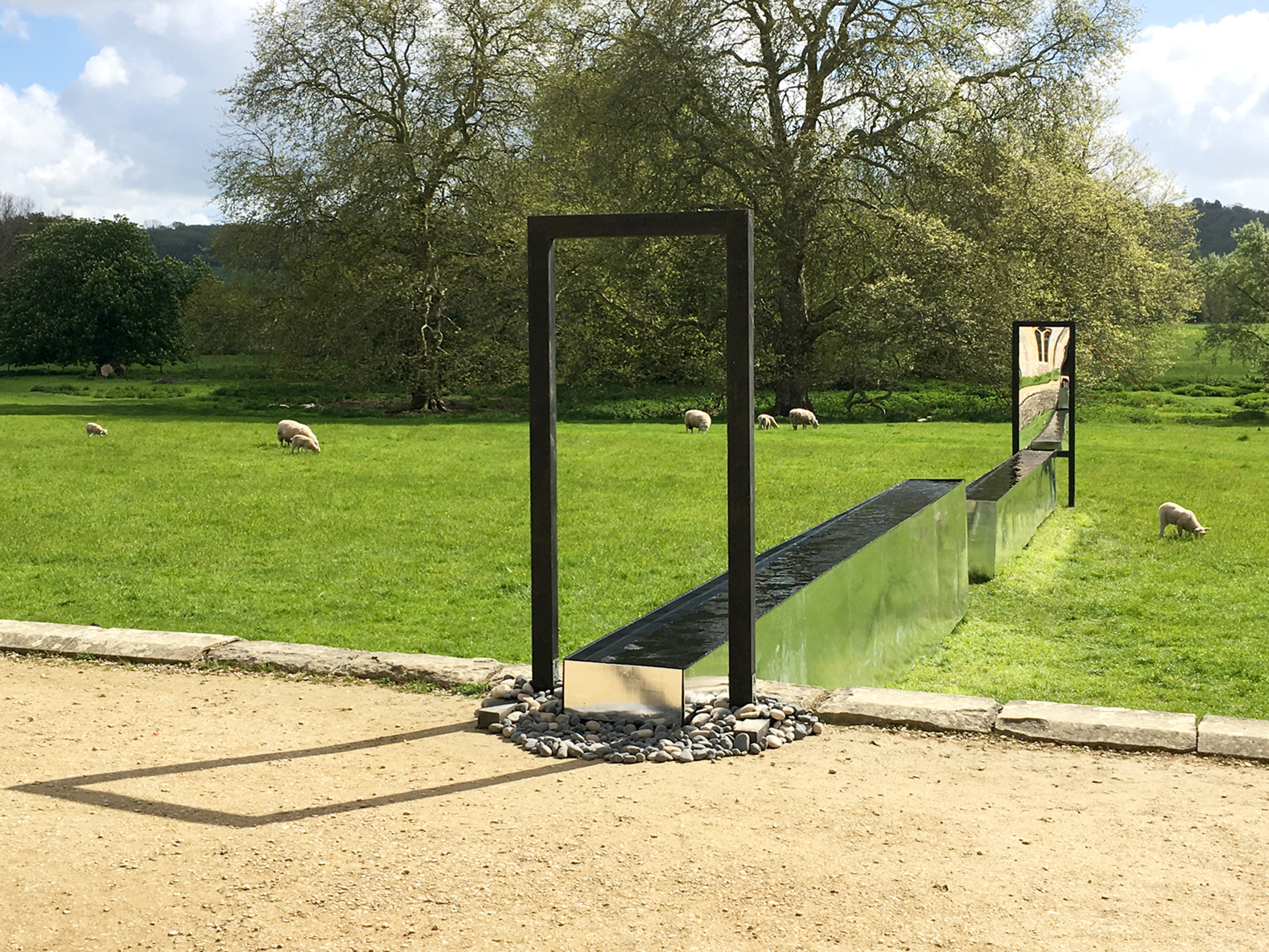Channel of Peace art installation by ALT-Architecture at Lacock Abbey National Trust - channel of reflective water - frames in landscape - water meadow with sheep
