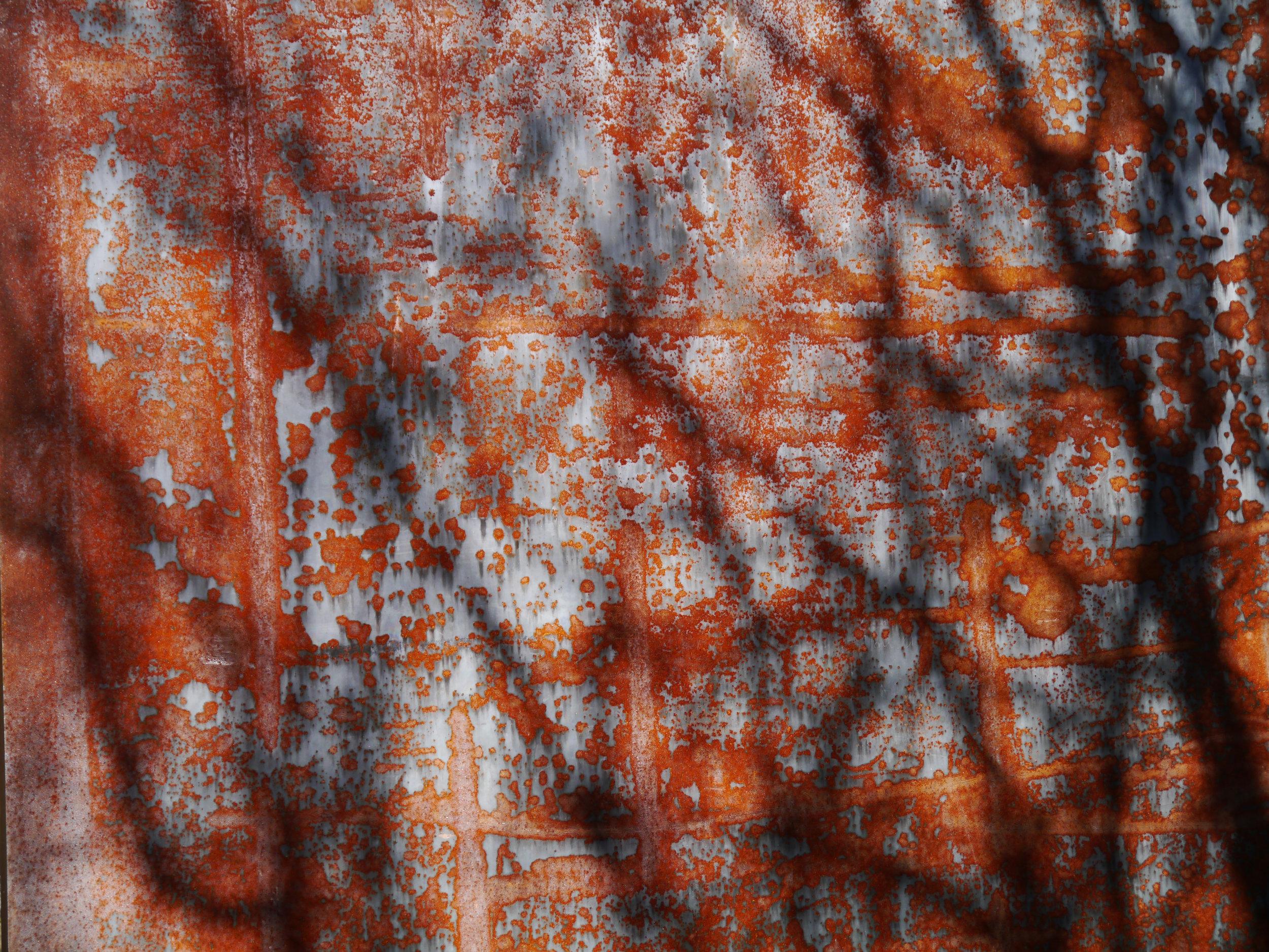 Dappled light through trees on rusted weathered steel sculpture - Richard Serra Walking is Measuring, 2000 Corten steel (2 elements) 532 x 244 x 15 cm; 386 x 244 x 15 cm Coll. Fundação de Serralves — Museu de Arte Contemporânea, Porto