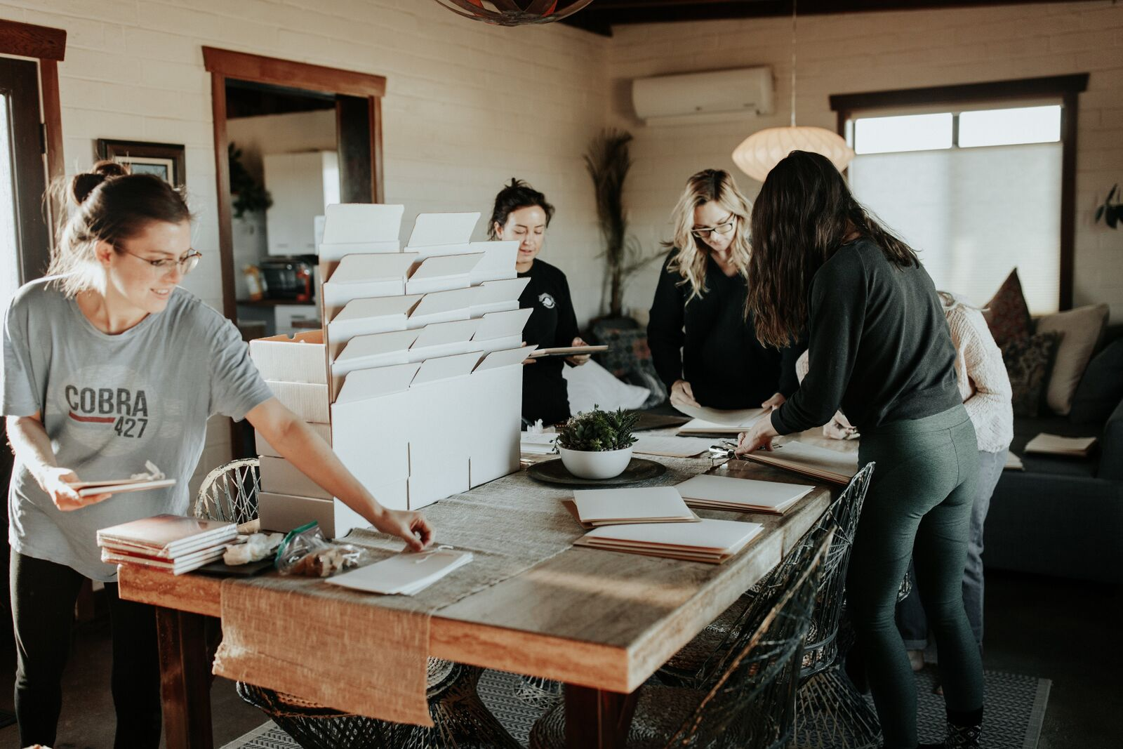 Sustainable event planners setting up green and recycled invitations and decorations for wedding celebration