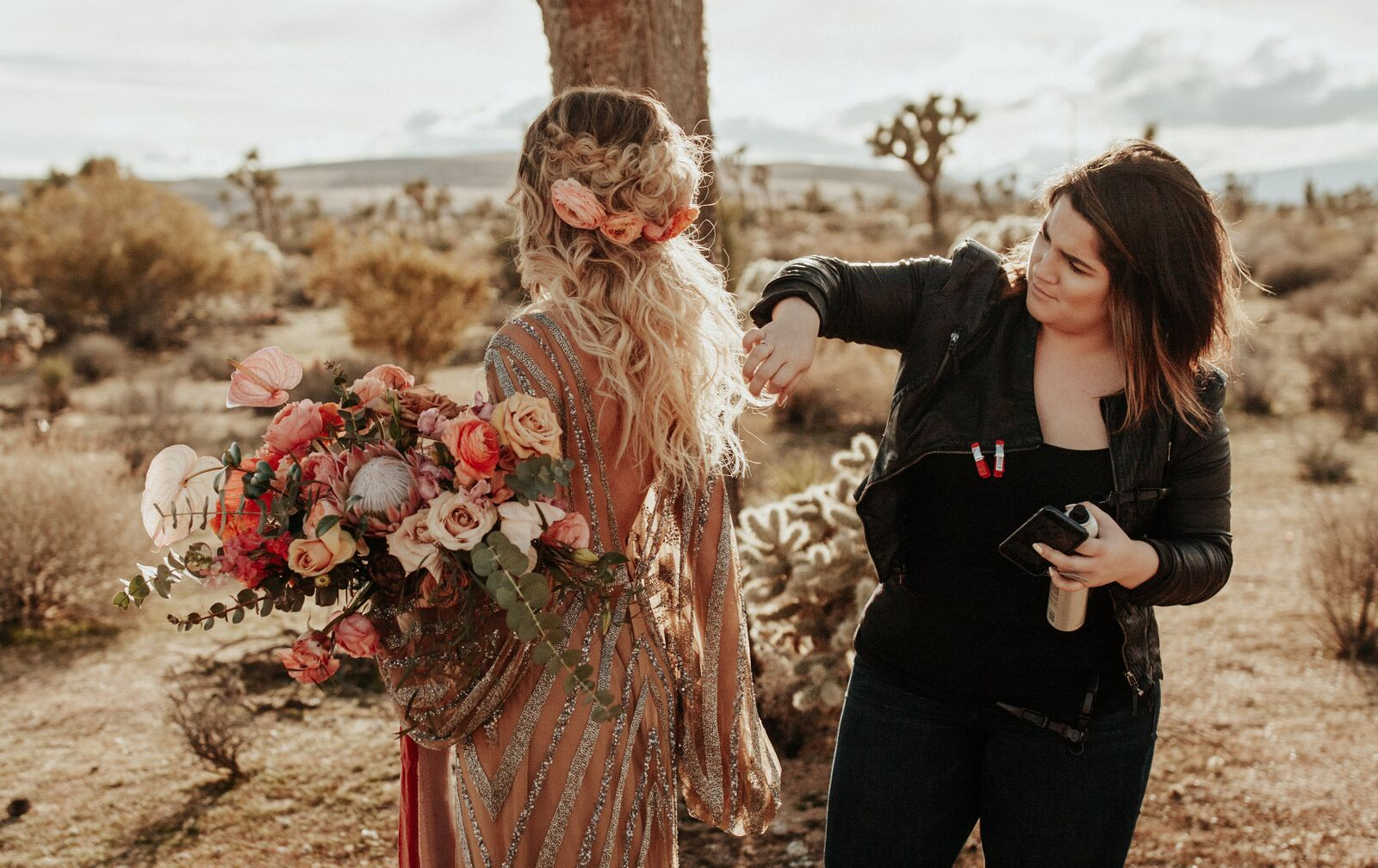 Outdoor photo shoot with engaged bohemian bride with hair stylist holding sustainable and organic peach flower bouquetOutdoor photo shoot with engaged bohemian bride with hair stylist holding sustainable and organic peach flower bouquet