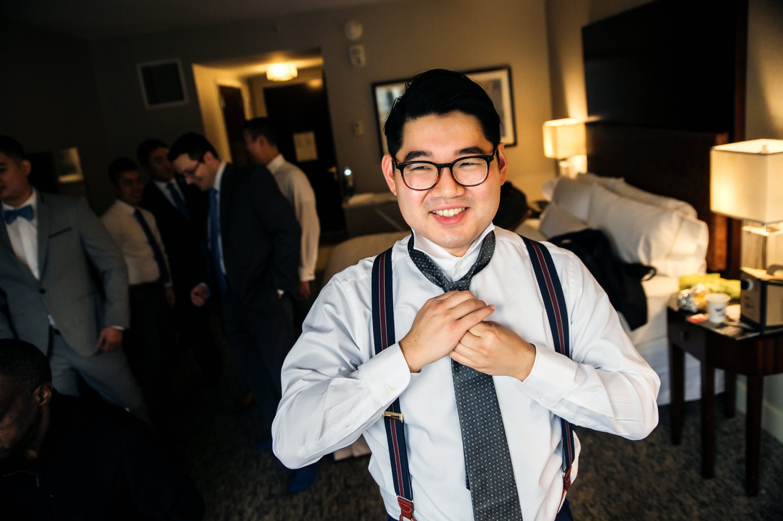 Portait of asian groom tying his 20's tie while getting ready at the Westin hotel room with groomsmen