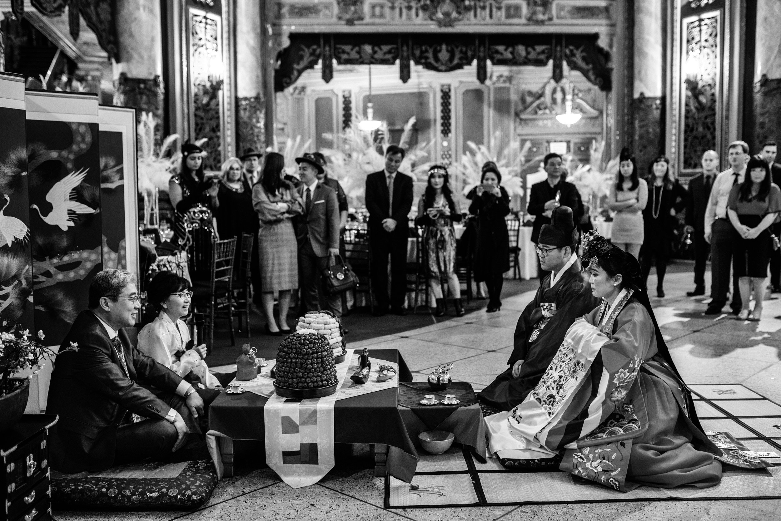 Black and white photo of traditional Korean tea ceremony during sustainable wedding reception of bride and groom celebrating a momentus occasion while wearing native garb