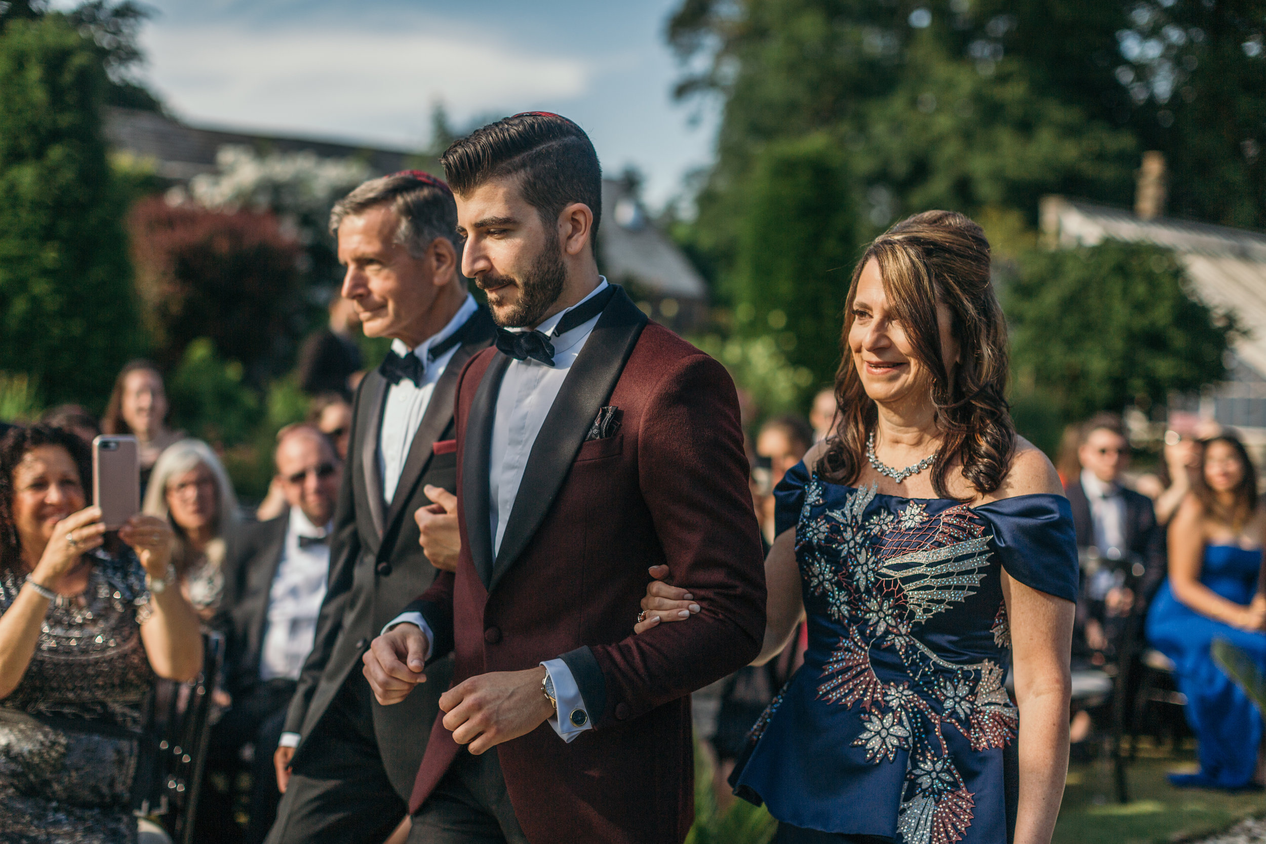 Groom walking down aisle with parents in Scotland castle outdoor destination wedding